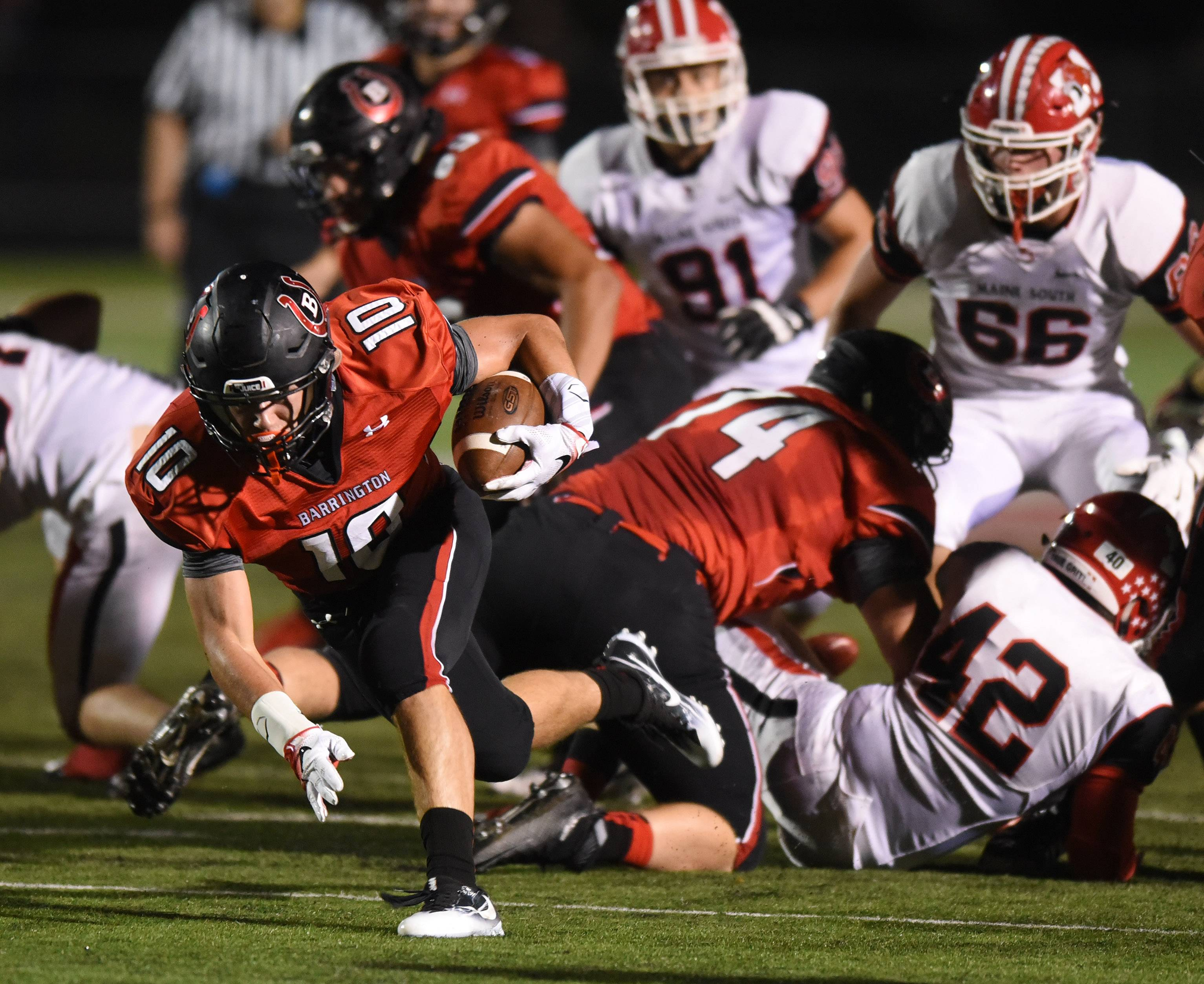 Barrington's Logan Moews stays on his feet after breaking through the Maine South defense during Friday's football game at Barrington.