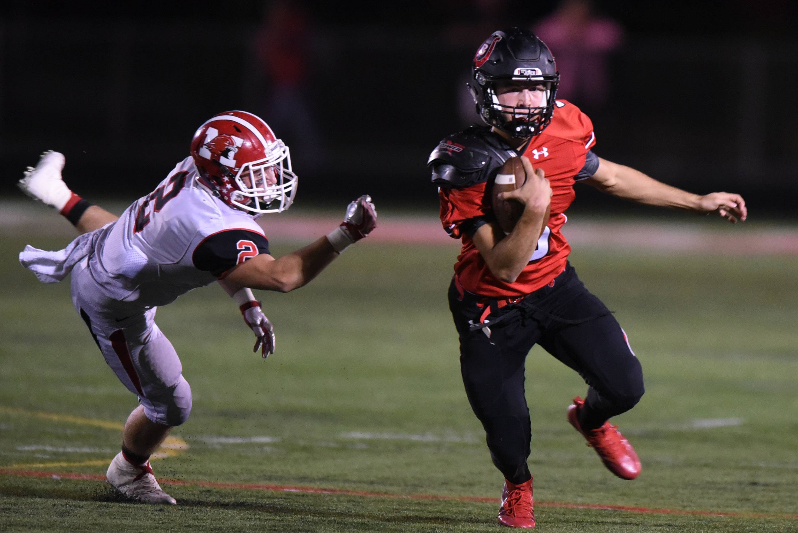 Barrington quarterback Ray Niro eludes Maine South's Matt Fortune as he carries the ball during Friday's football game at Barrington.