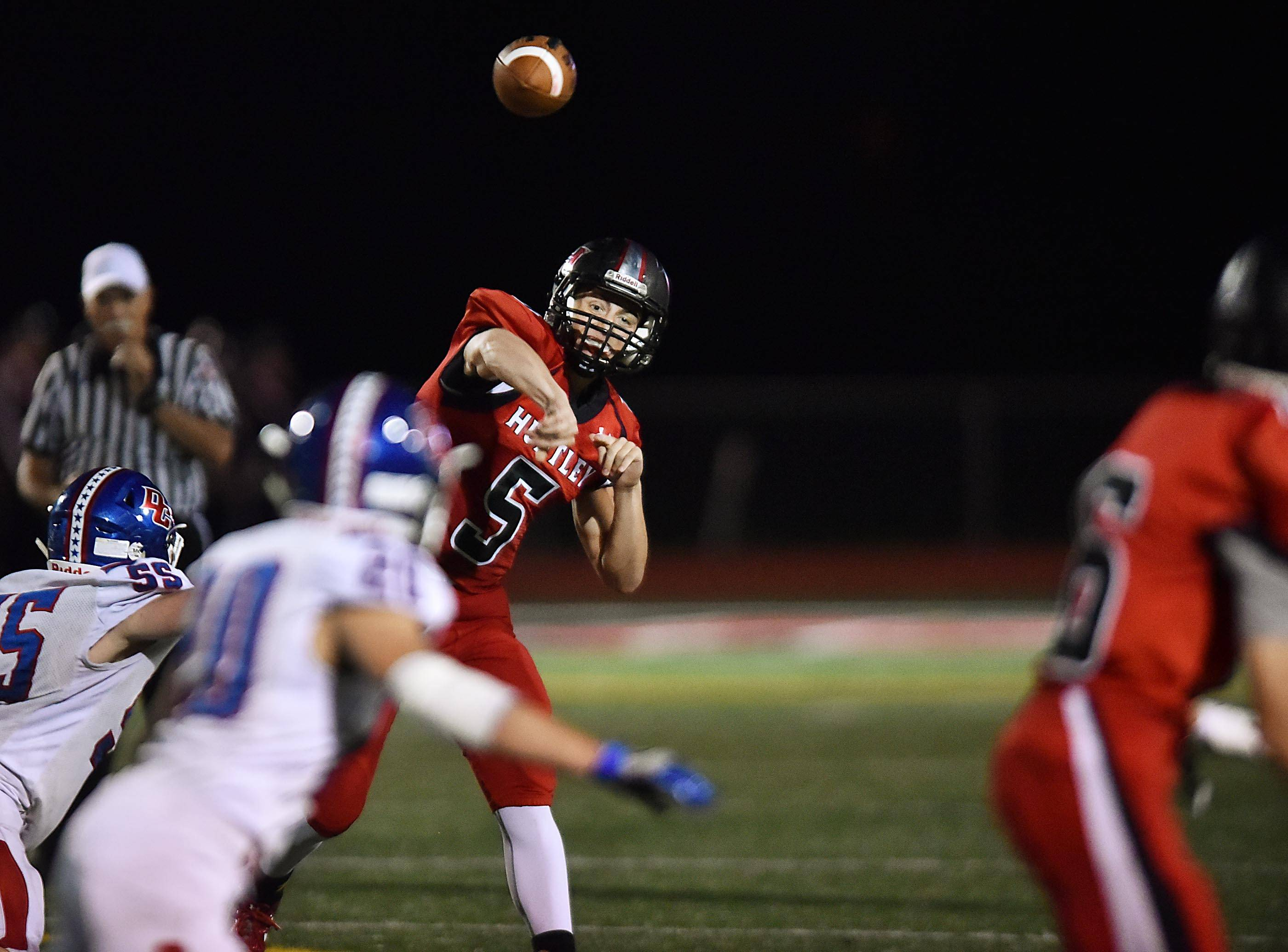 Huntley quarterback Eric Mooney throws to Brian O'Mara for a long gain against Dundee-Crown Friday in Huntley.