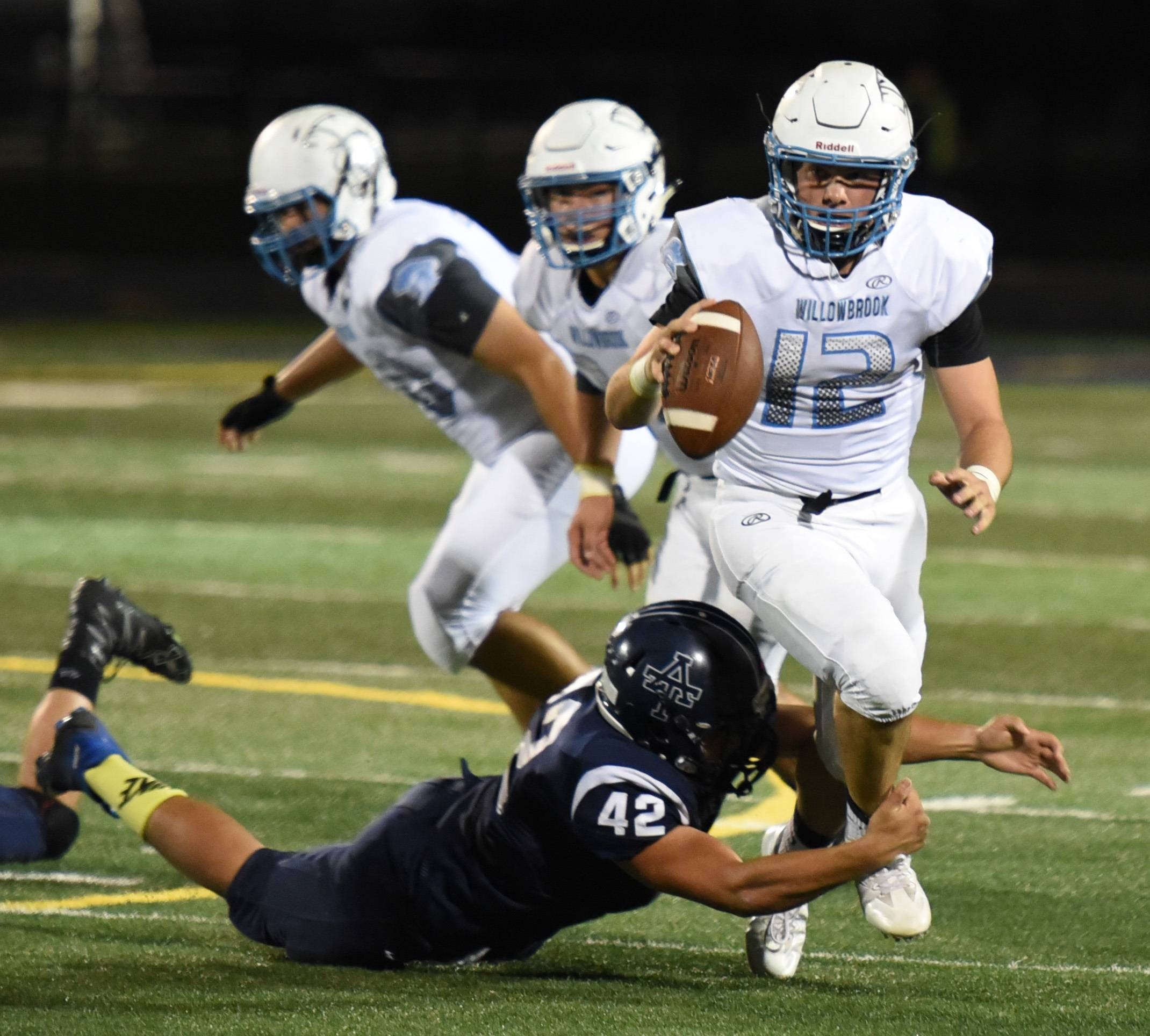 Paul Michna/pmichna@dailyherald.comAddison Trail's Juan Bracamontes  (42) attempts to bring down Willowbrook's  M.J.  Ranieri  (12) during the Willowbrook at Addison Trail football game Friday.