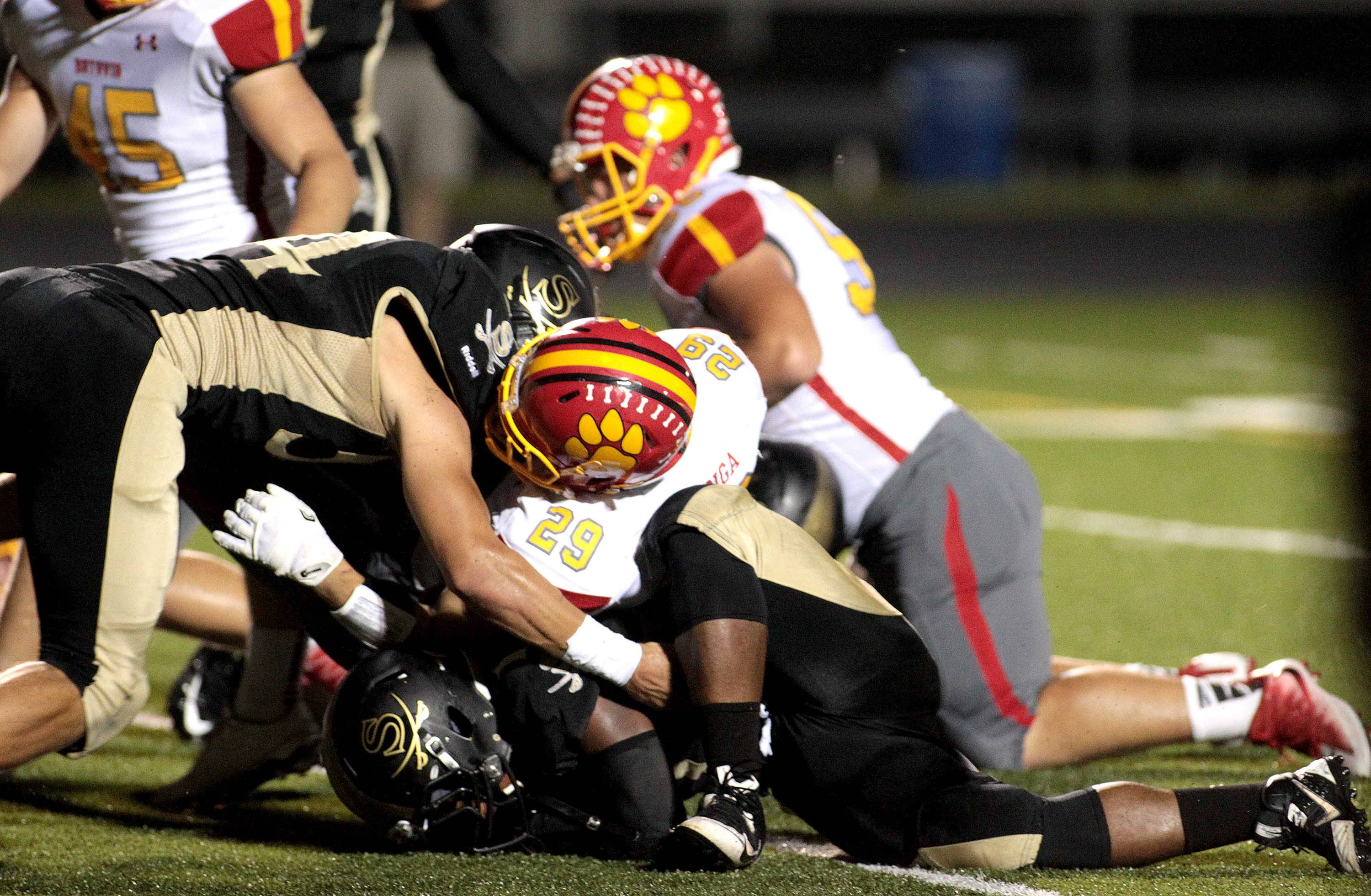 Batavia's Matthew Huizinga (29) gets lost in the pile after scoring a touchdown during a game at Streamwood Sept. 9.