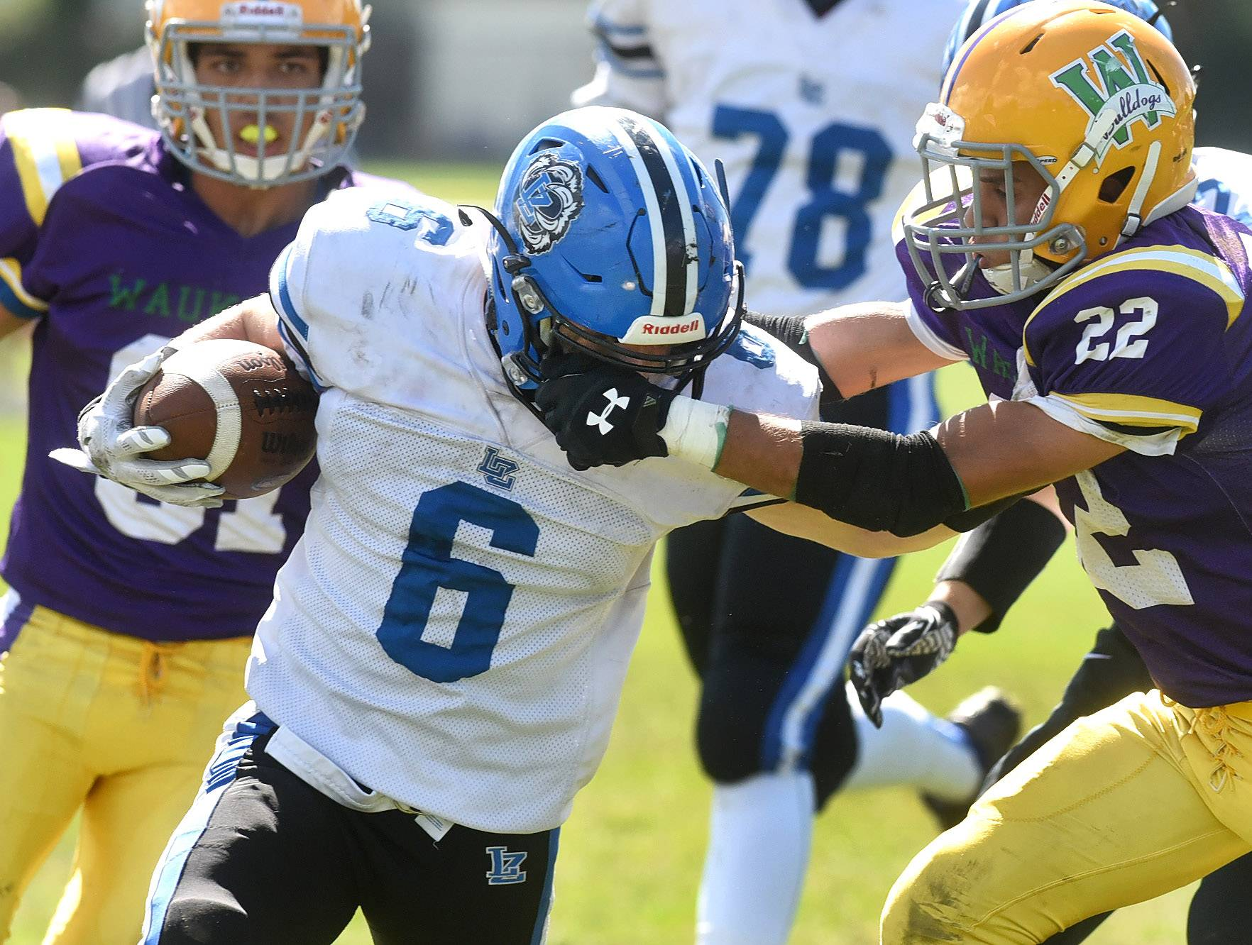 Lake Zurich running back Joey Stutzman gets facemasked by Waukegan's Anas Abushamt during second-quarter action at Waukegan on Saturday.