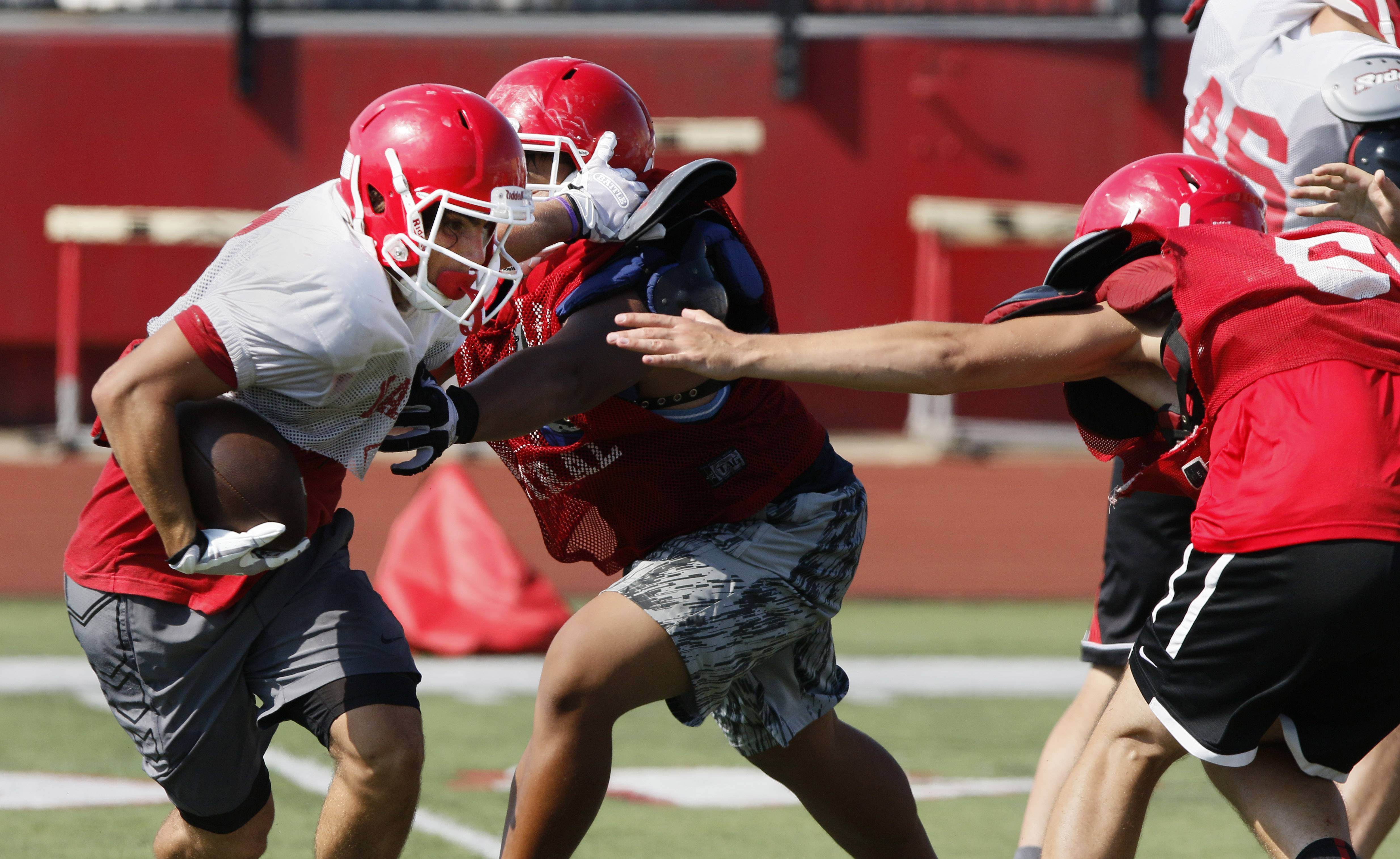 Naperville Central's A.J. Deinhart navigates his way through the defense during the first week of football practice.