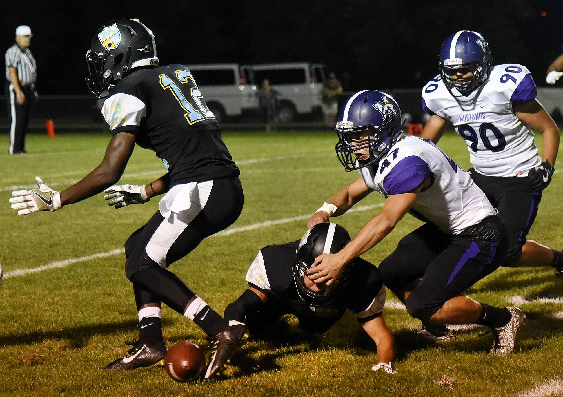 Maine West's Rafael Ynocencio tries to recover a fumble as the ball rolls out of bounds in first half against visiting Rolling Meadows on Friday.