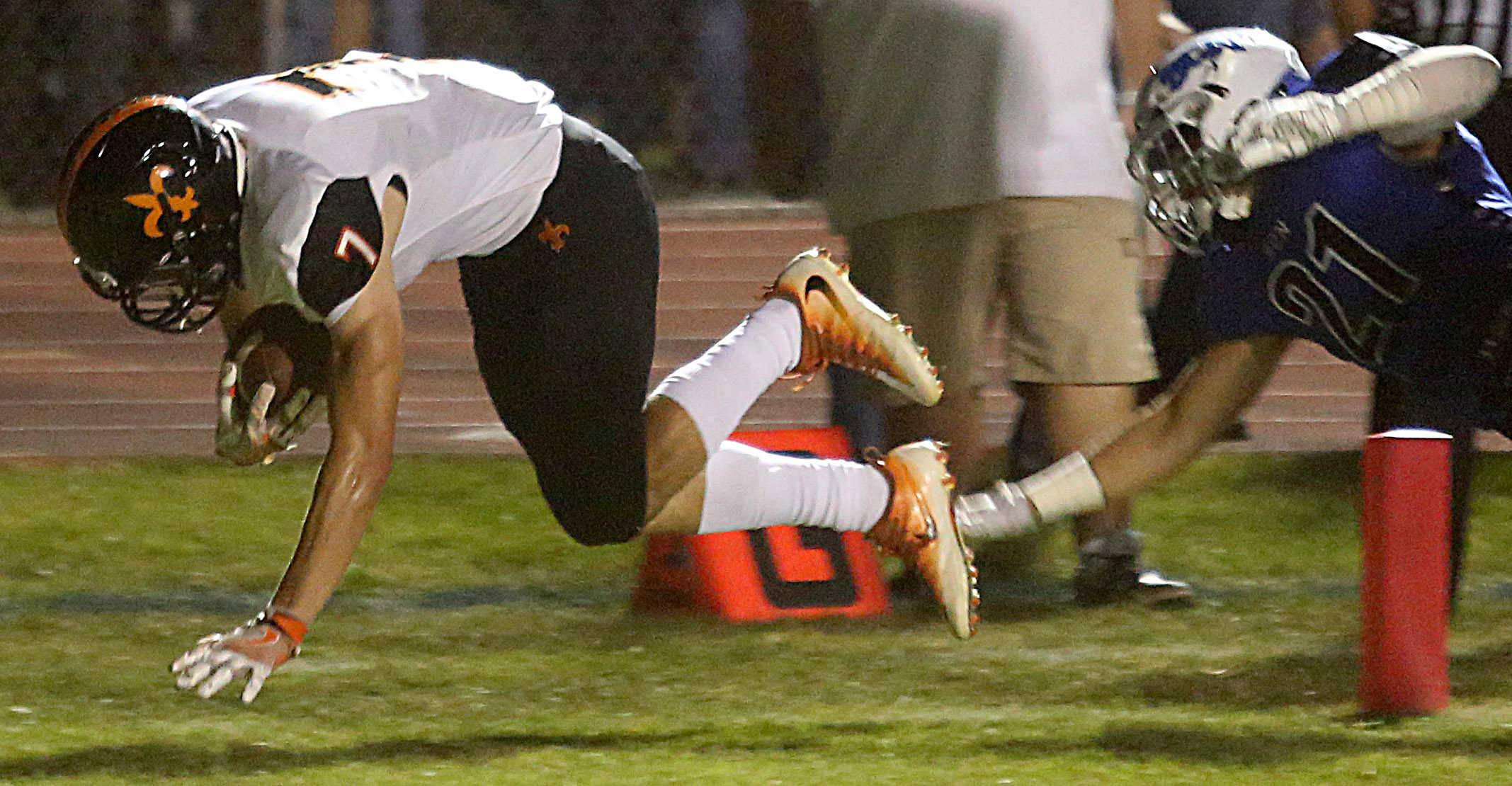St. Charles East's Nicholas Garlisch tumbles into the end zone for a touchdown against St. Charles North Friday.