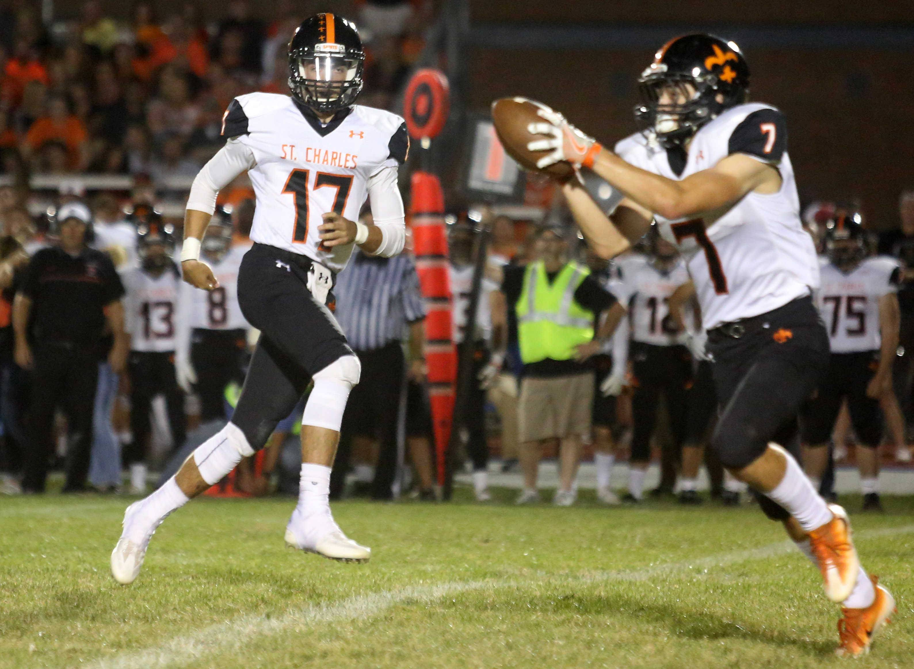 St. Charles East quarterback Zachary Mitchell pitches the ball to Nicholas Garlisch during the Crosstown Classic football game at St. Charles North Friday night.