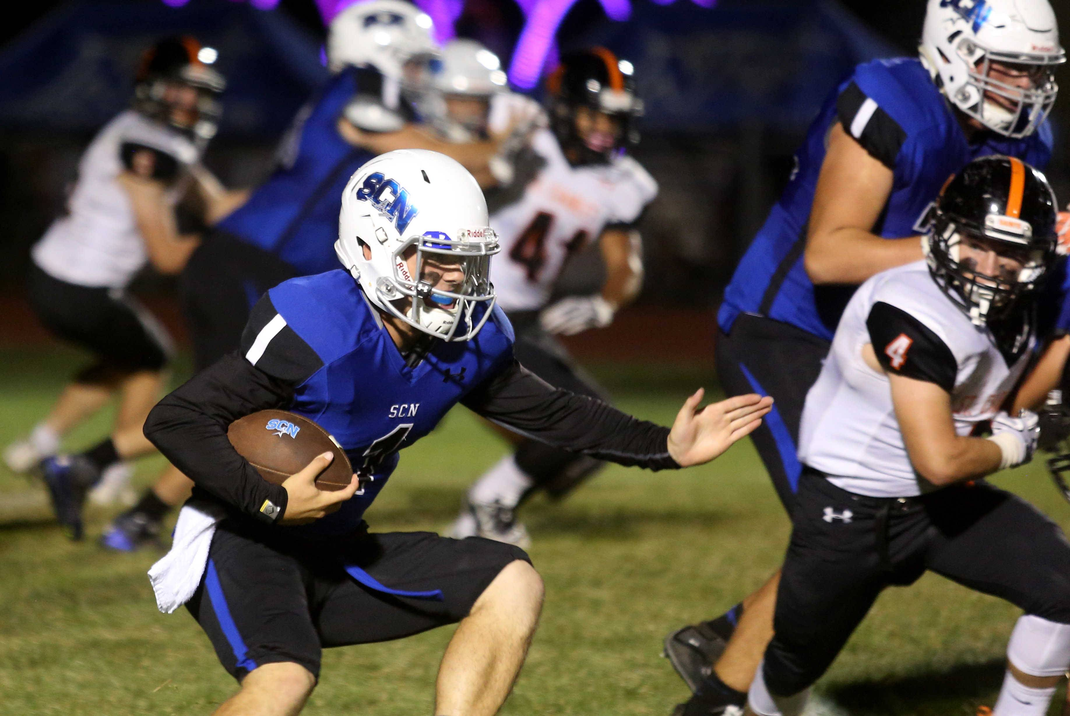 St. Charles North quarterback Zach Mettetal runs the ball during the Crosstown Classic football game at St. Charles North Friday night.