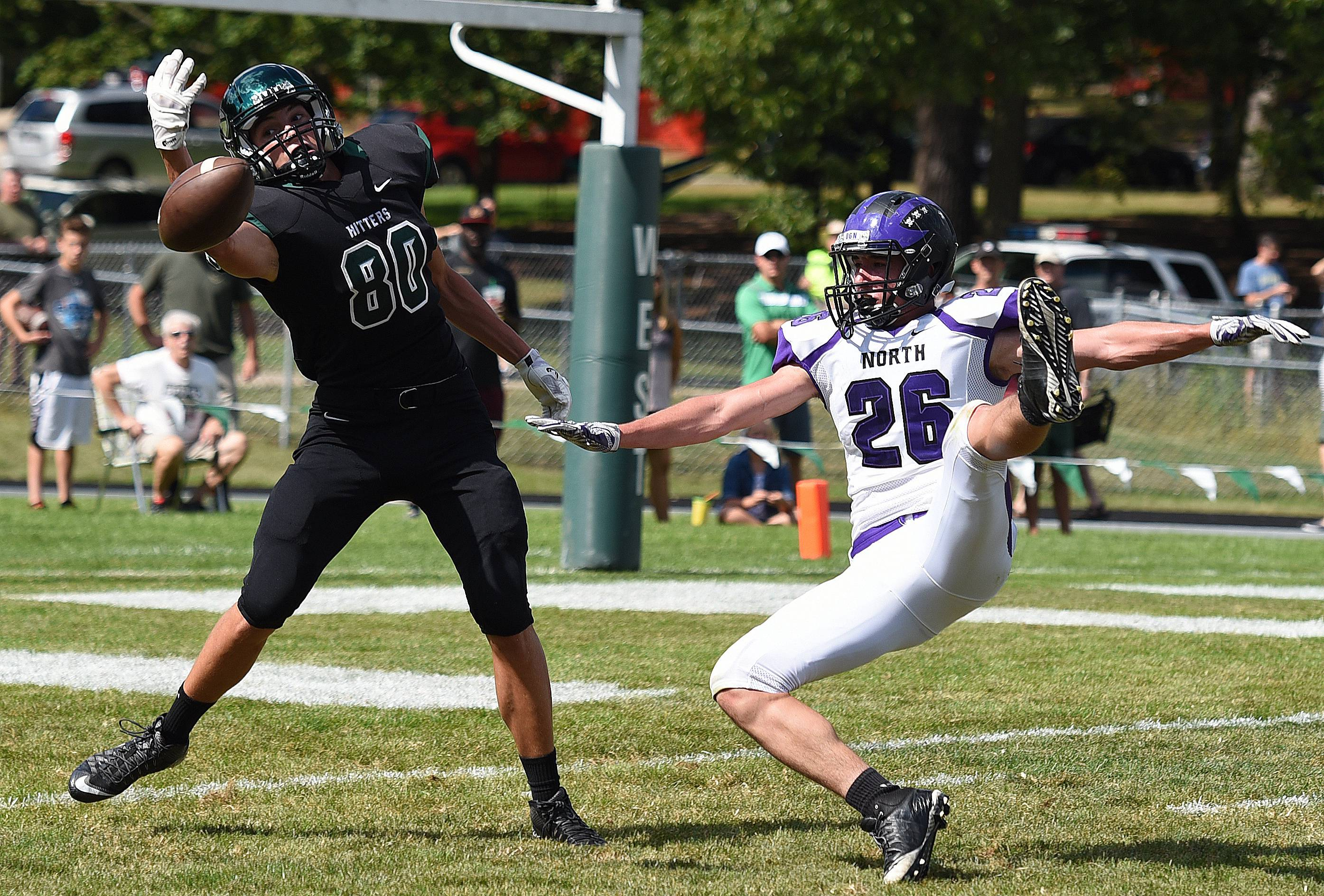 Glenbard West's Alec Pierce (80) reaches for the ball as Downers Grove North's Joe Keys (26) falls back during the Downers Grove North at Glenbard West football game Saturday.