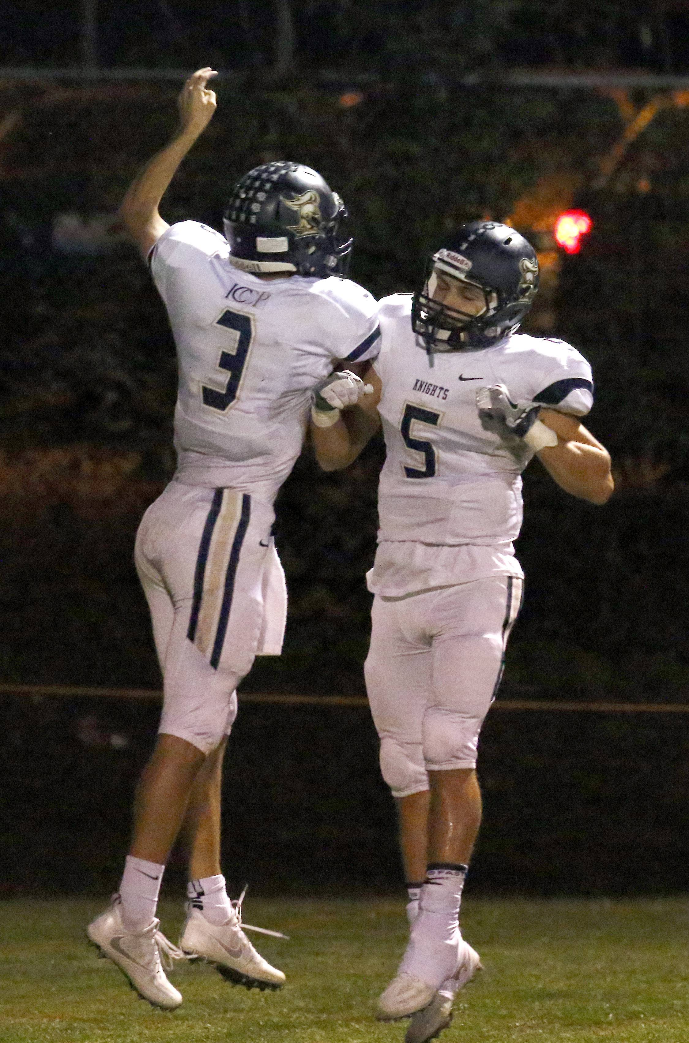 IC Catholic's Luke Ricobene celebrates with teammate Matt Sutton (5) after his touchdown at Greg True Field in Elgin Friday night.