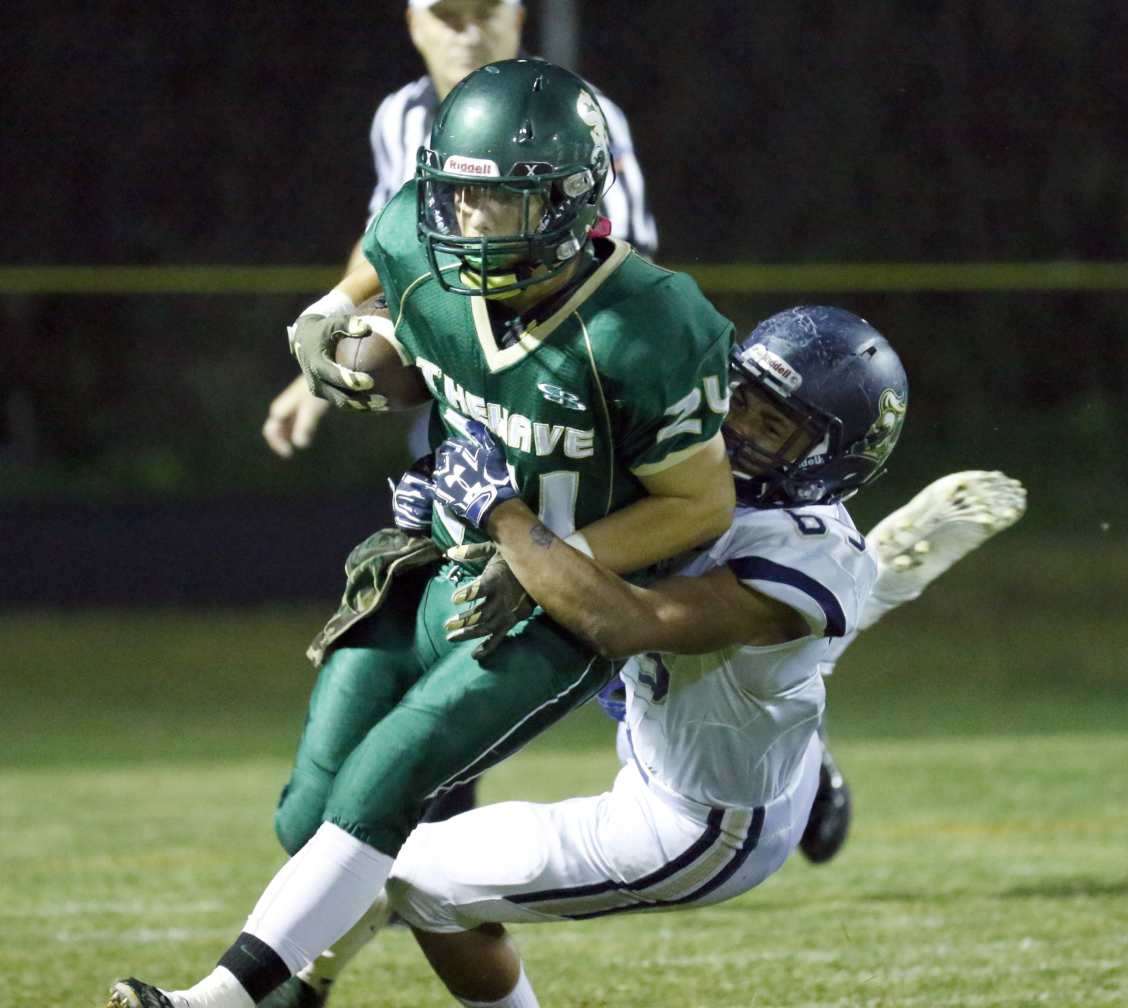 St. Edward's Angel Garcia tries to break free from IC Catholic's Kemon Reese Friday night at Greg True Field in Elgin.