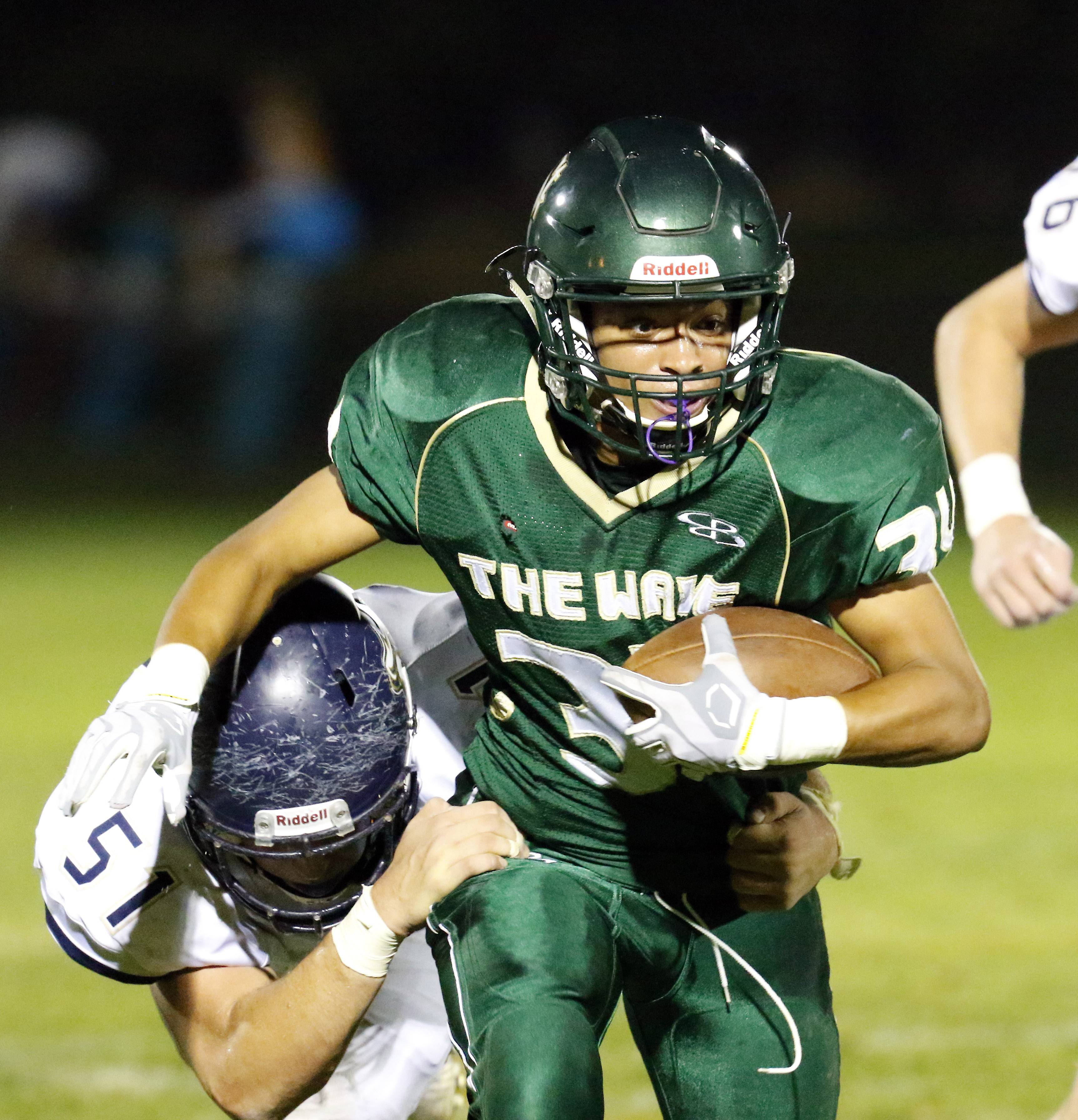 St. Edward's Daniel Falco is wrapped up by IC Catholic's Dylan Packer at Greg True Field in Elgin Friday night.