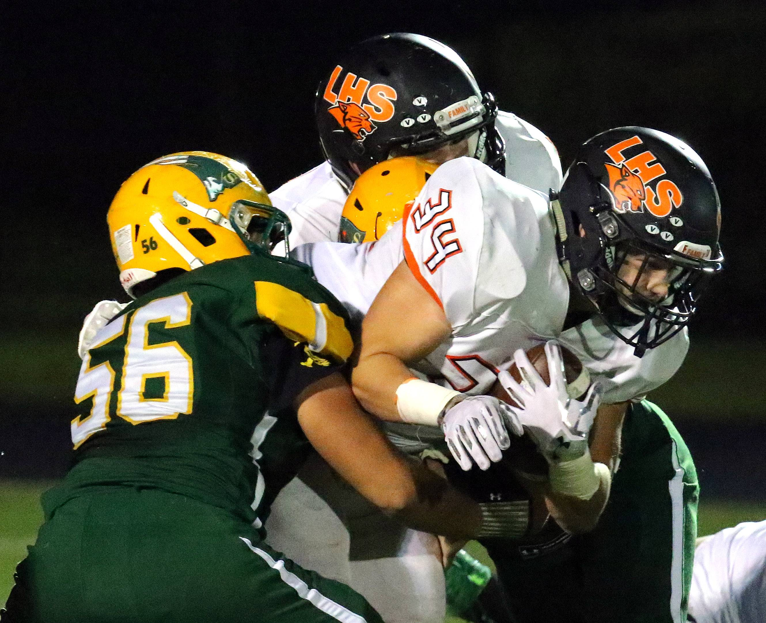 Libertyville's Brendan Bazar (34) runs for some tough yards as Stevenson's Tyler Kozub tries to wrap him up Friday night at Stevenson.