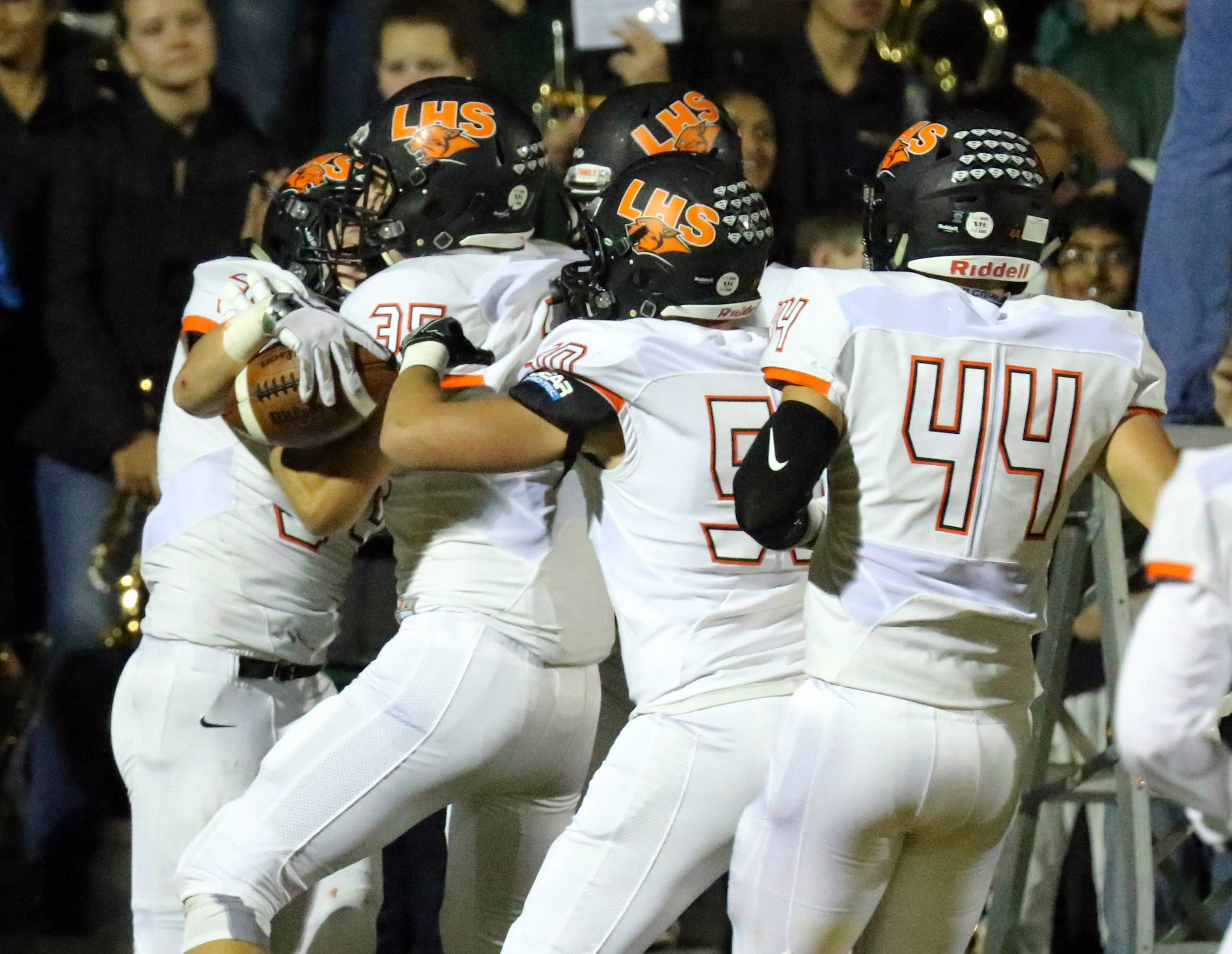 Libertyville's Brendan Bazar, left, is mobbed by teammates after a kickoff return for a touchdown on Friday night at Stevenson.