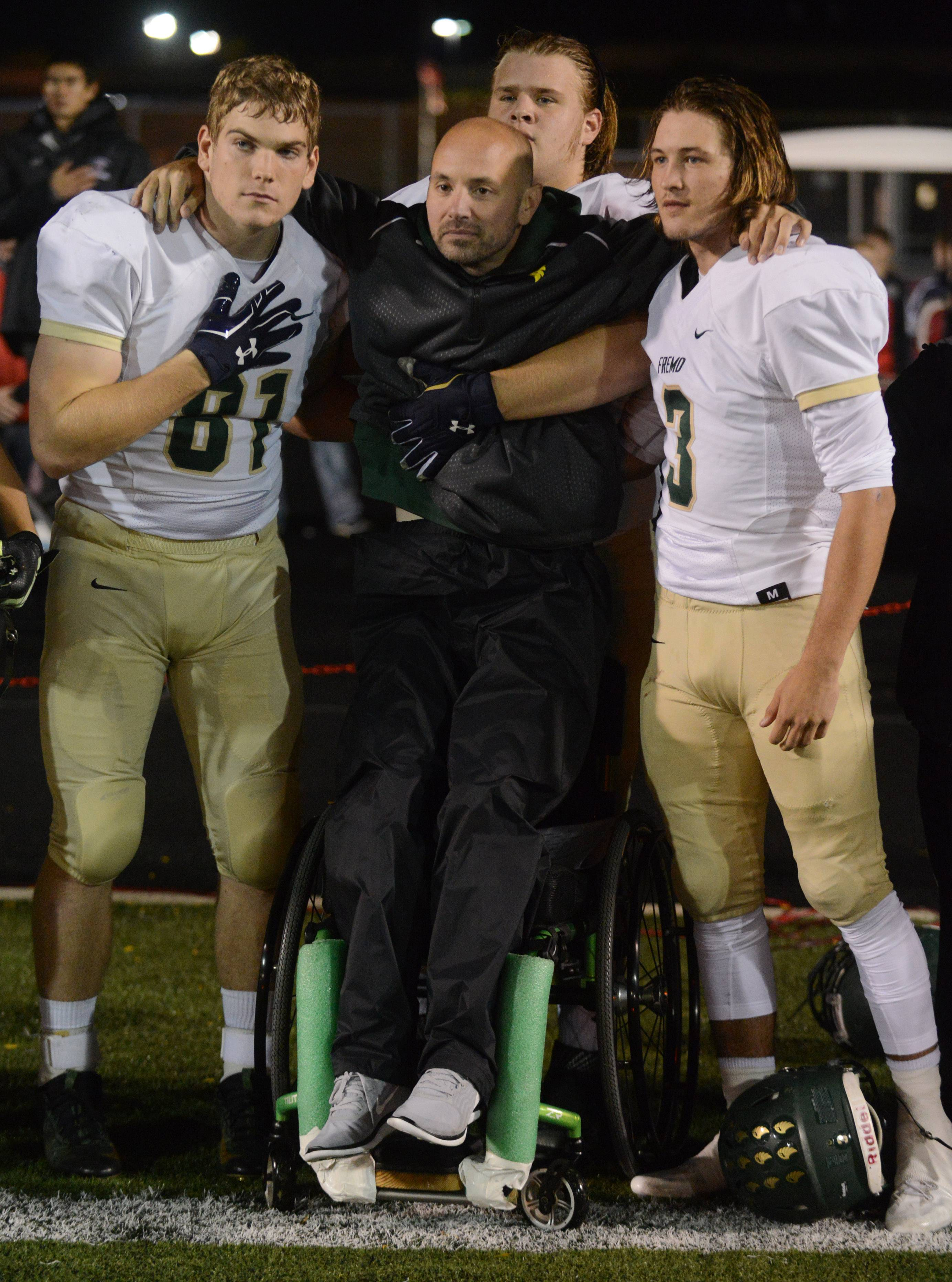 Fremd football players, from left, Austin Schwantz, Ethan Hanson and Jake Haas, help the team's special team's coach, paraplegic Navy veteran Brock Schiffer, stand during the National Anthem prior to Friday's game against Palatine. The gesture was meant as a counterpoint to those who would choose to kneel during the anthem as a protest.