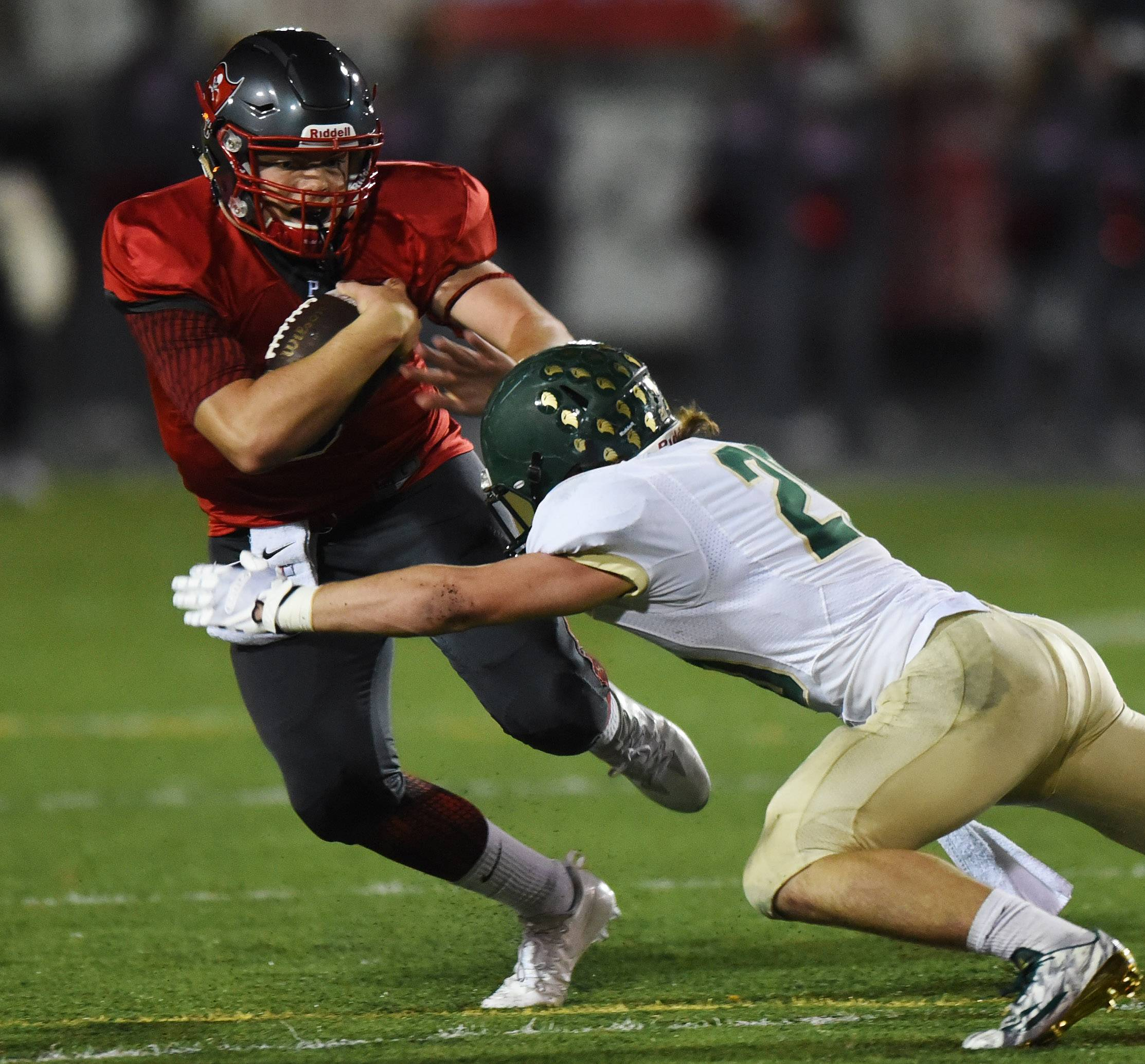 Palatine quarterback Zachary Oles carries the ball before being tackled by Fremd's Joe Schneider during Friday's game.