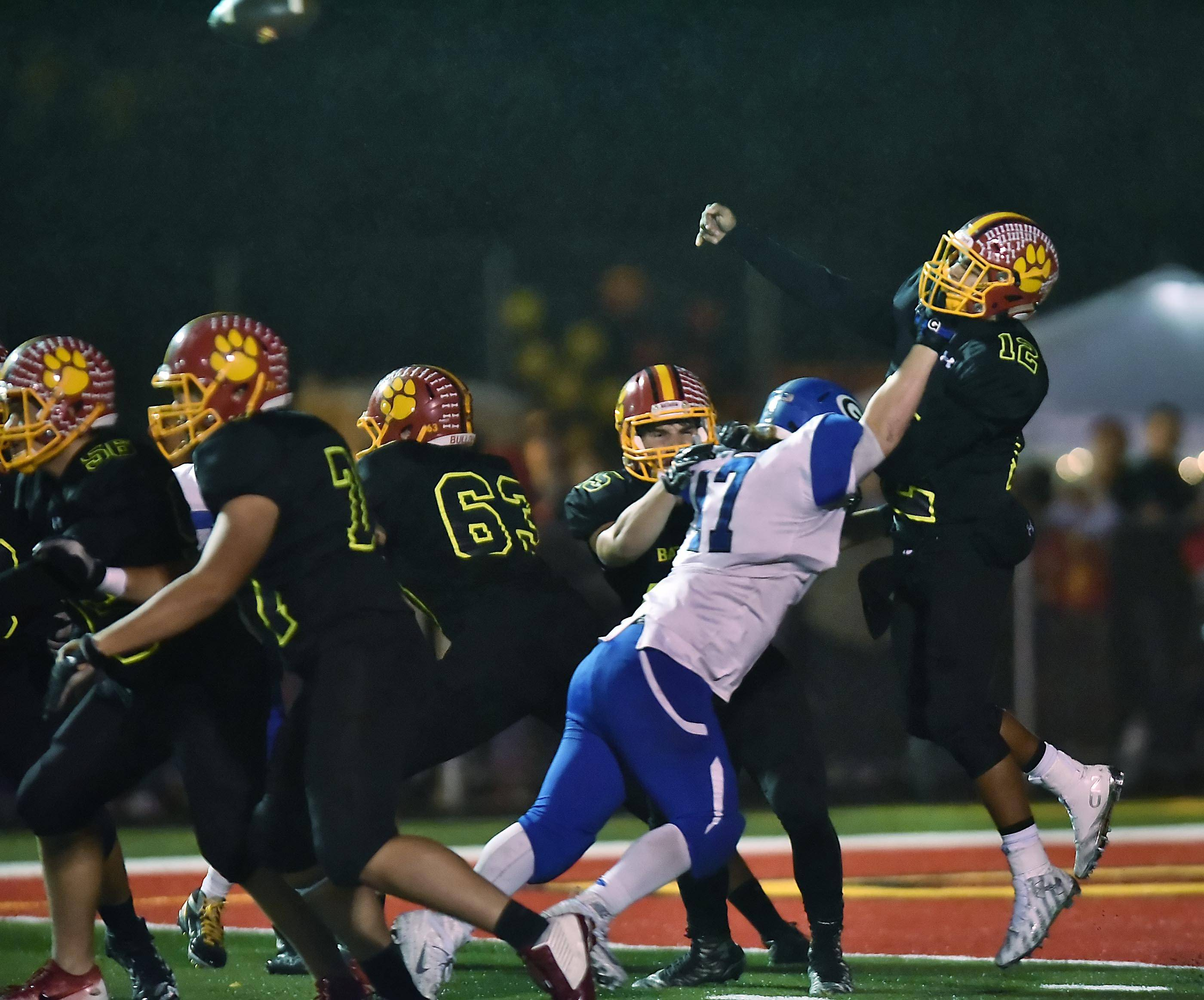 Batavia's Riley Cooper is able to make a pass in the rain as Geneva's Blake McAvoy hits him in the second quarter at Batavia Friday night.