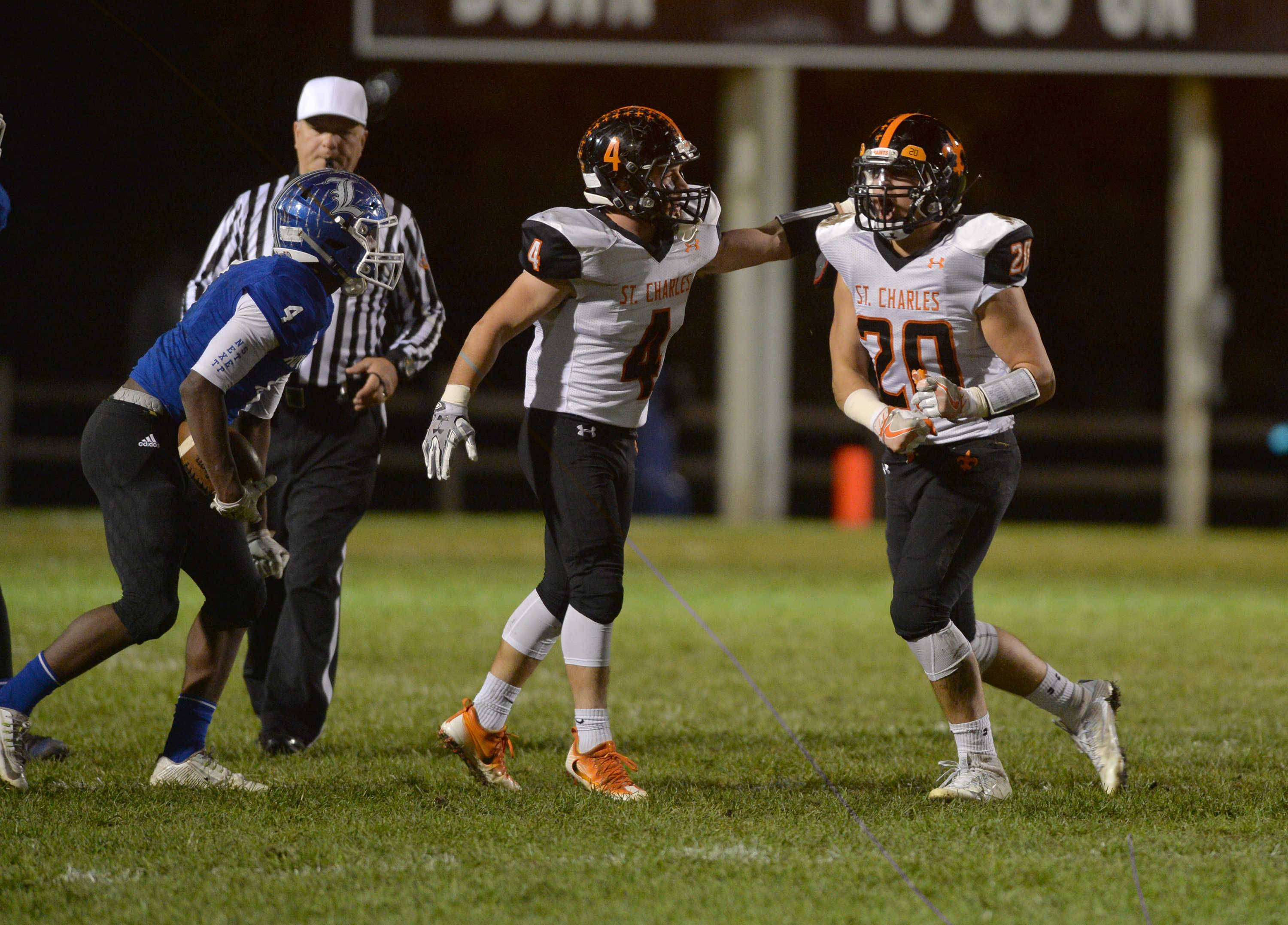 St. Charles East linebackers Nicholas Piaskowy and Abe Swanson celebrate after stopping Larkin running back DJ Ball in the second quarter of their Upstate Eight River contest Friday night at Memorial Field in Elgin.
