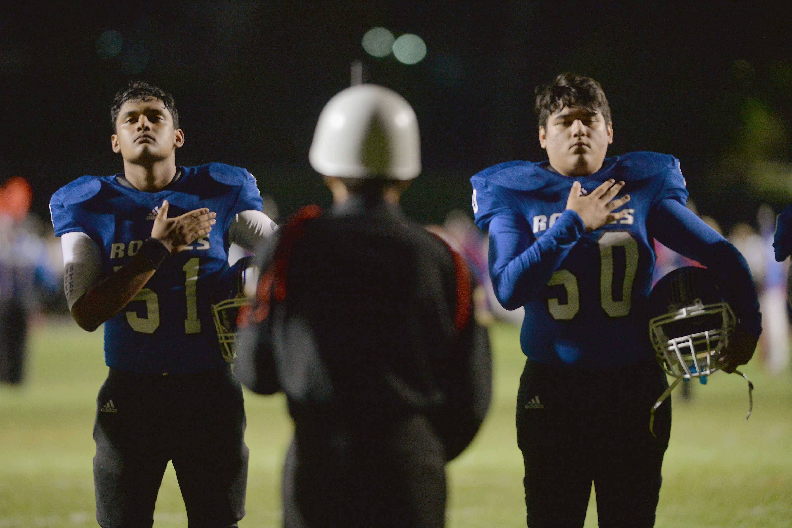 Larkin linebackers Manny Cruz, left, and Jose Bosque stand at attention for the national anthem before kickoff of their Upstate Eight game with St. Charles East Friday night at Memorial Field in Elgin. The school also honored 2003 graduate, Staff Sgt. Adam Thomas who died Monday in Afghanistan.