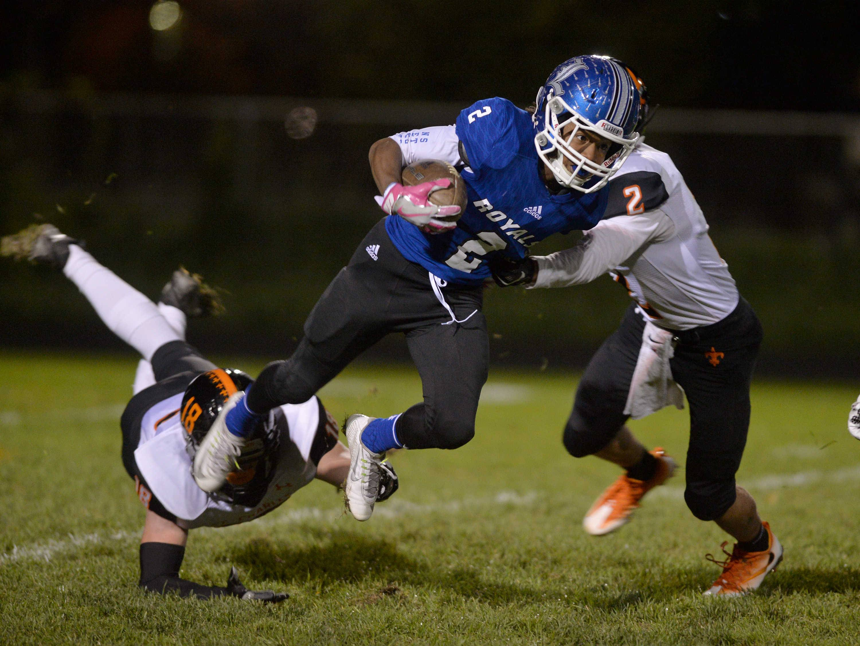 Larkin's Morris Kindrel fights for extra yardage on a return as St. Charles East's Stephen Abruzzo, left, and Justin Galante make the stop in the first quarter of their Upstate Eight River contest Friday night at Memorial Field in Elgin.