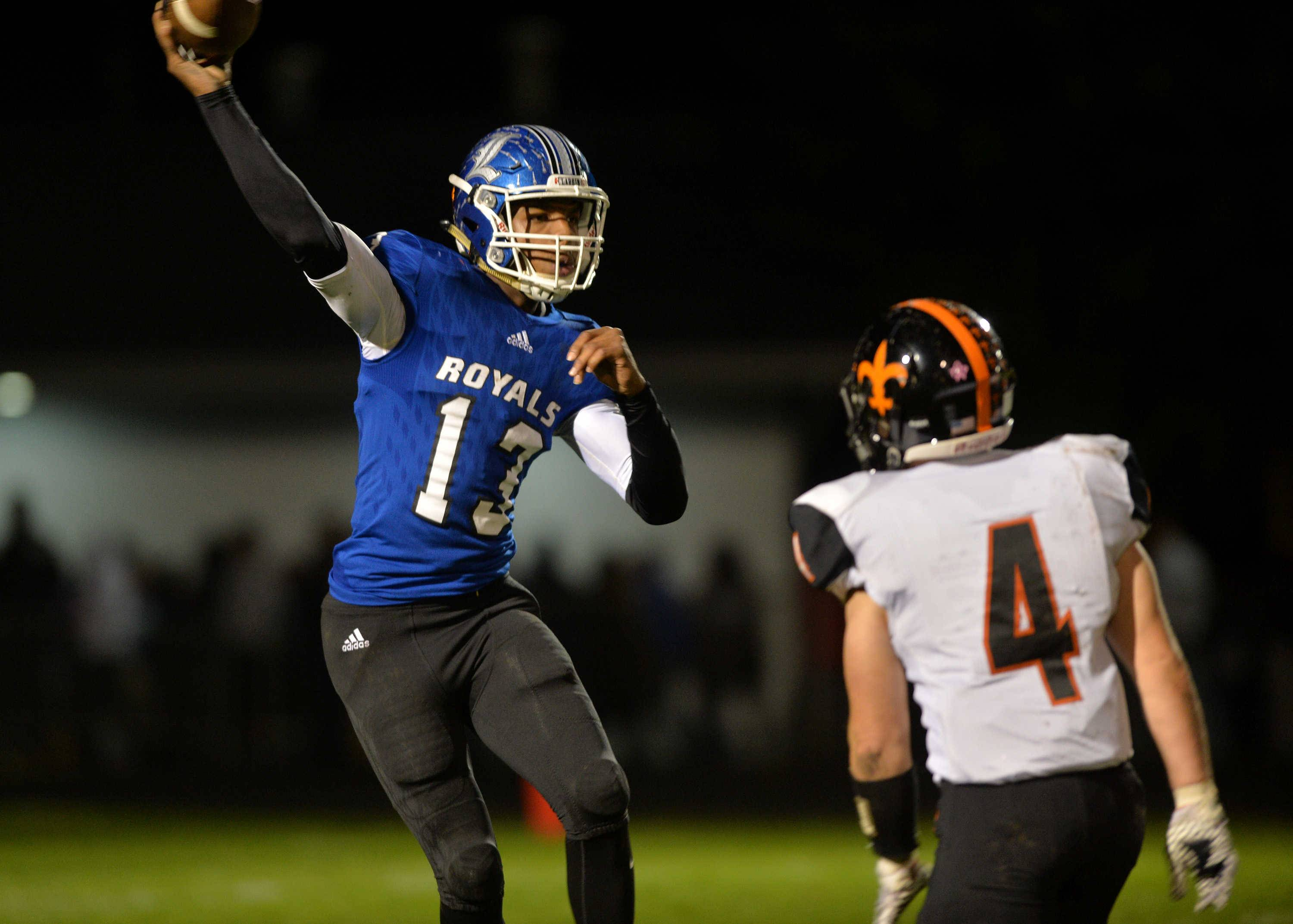 Larkin quarterback David Hibbler attempts a pass as St. Charles East's Nichikas Piaskowy defends in the second quarter of their Upstate Eight contest Friday night at Memorial Field in Elgin.