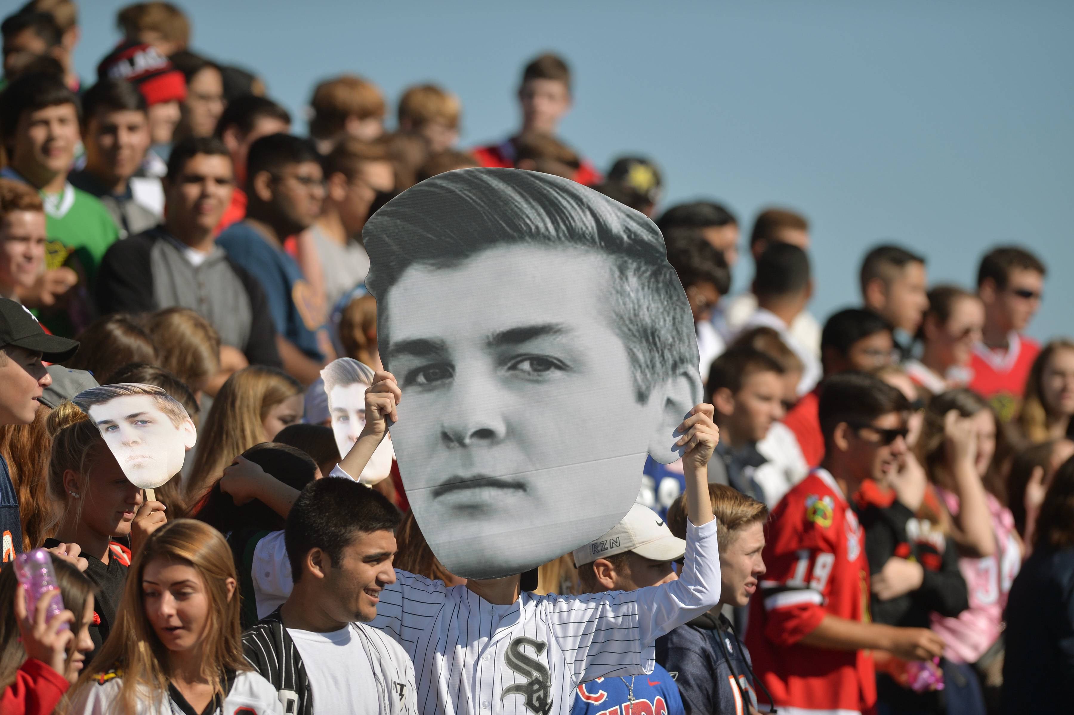 Students pass a giant photo of junior Cameron Montbriand in the Fear Nation student section during the Hawks' 42-7 win over East Aurora Saturday at Bartlett High School