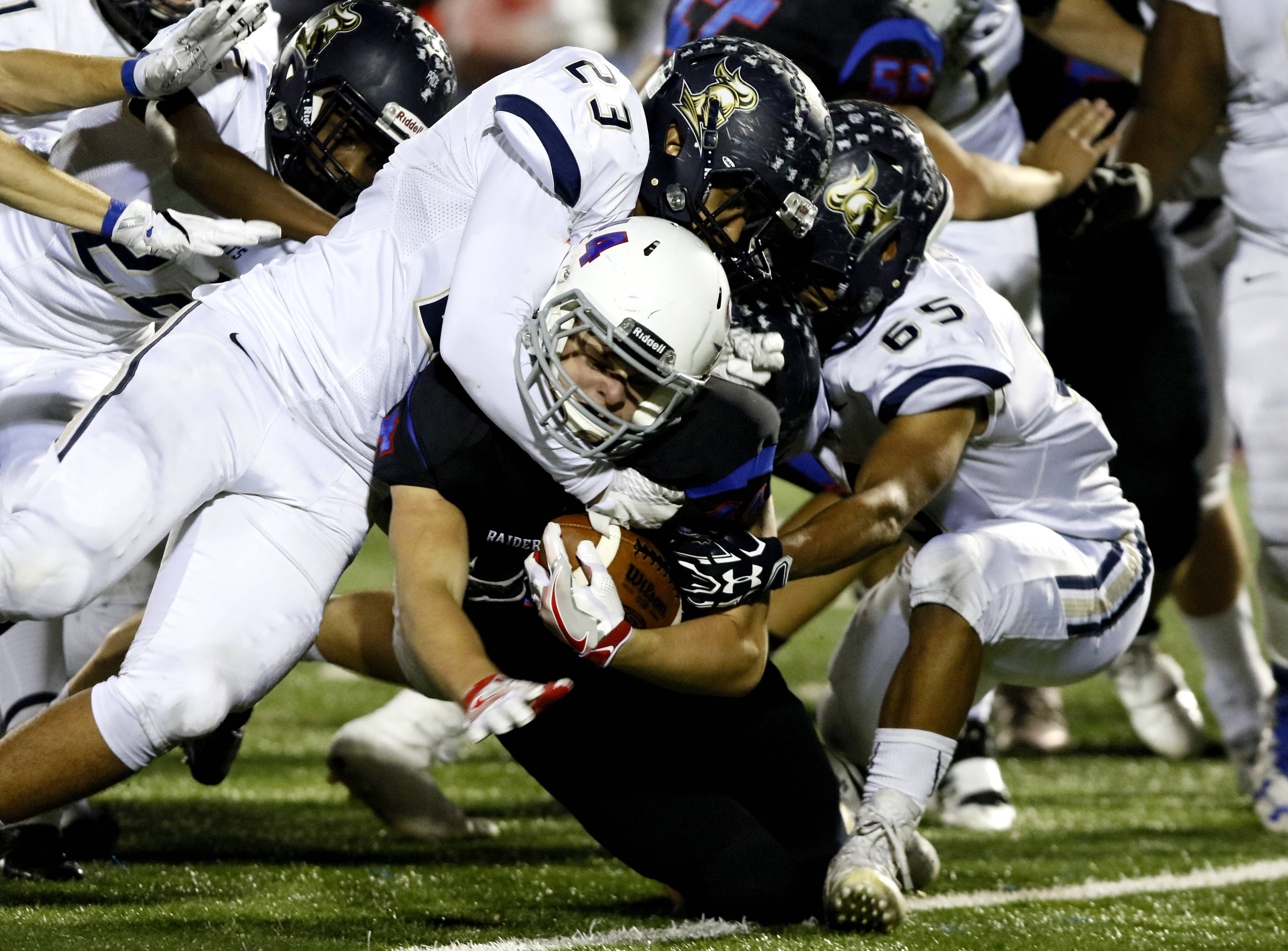 Glenbard South's Sean Cooke is tackled by IC Catholic Prep's Chris Johnson (23) and Kemon Reese (65), Friday, in Glen Ellyn.