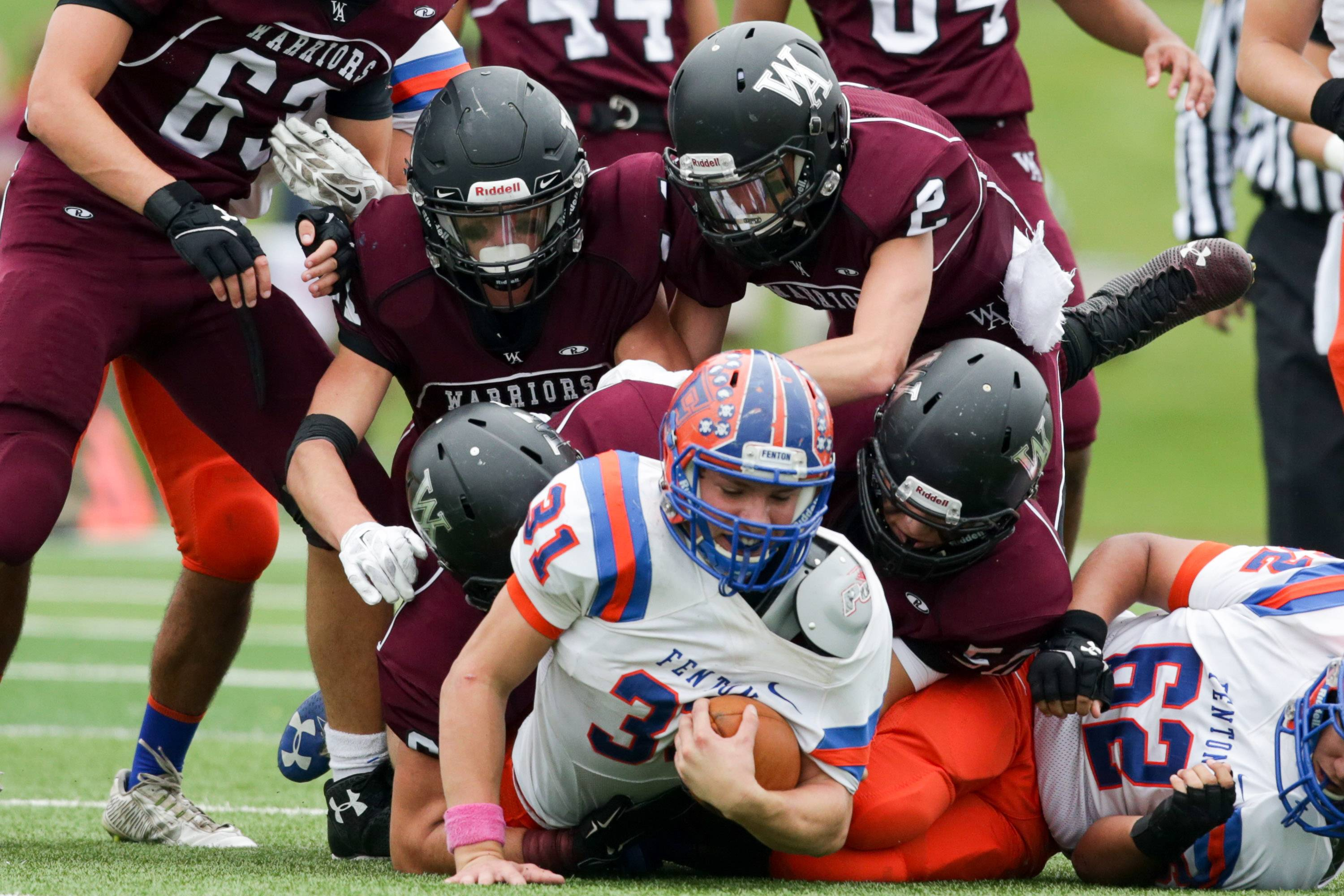 Photo by Sean KingFenton running back Dylan Butts (31) is brought down by four Wheaton Academy defenders at Wheaton Academy  in West Chicago Saturday.