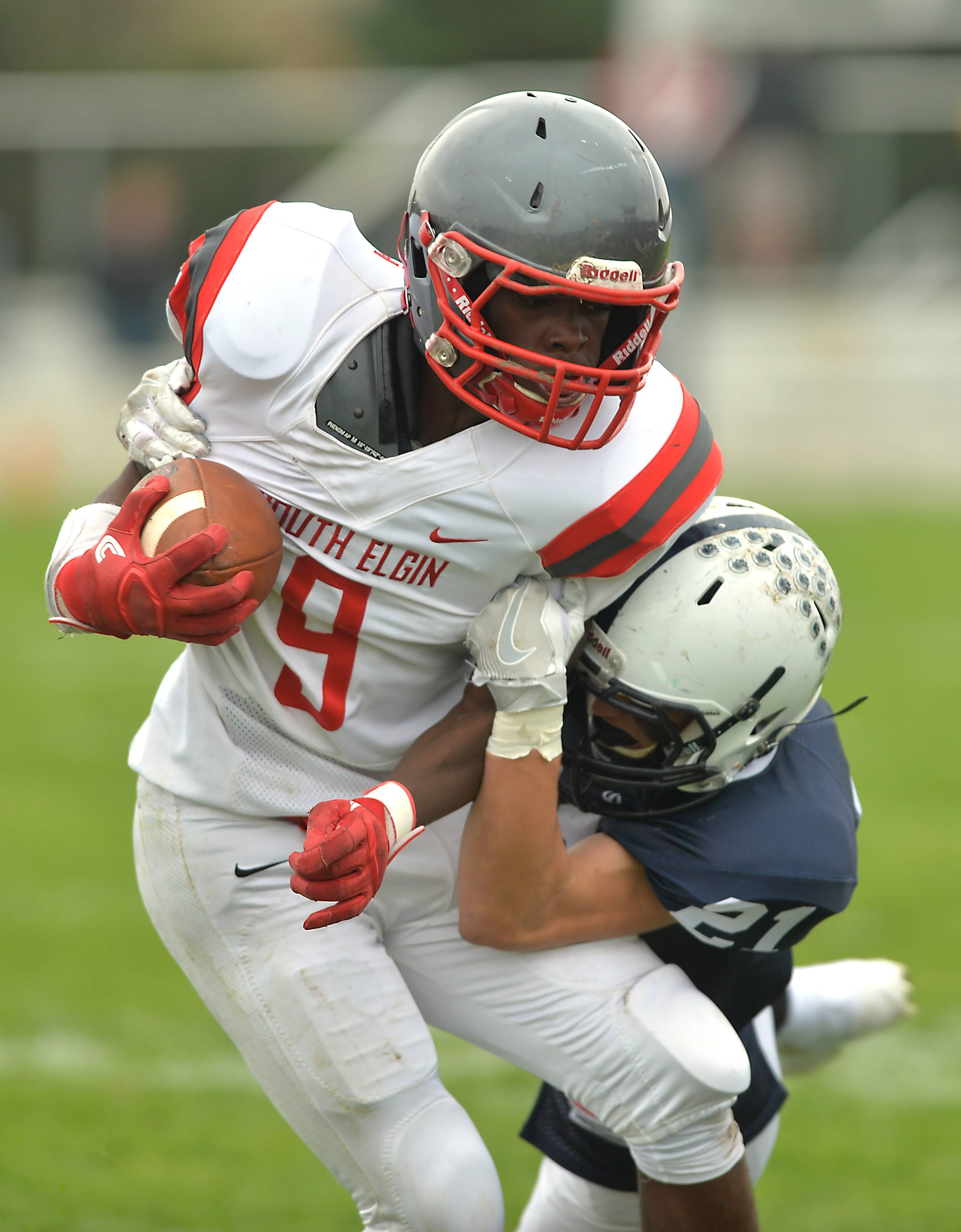 South Elgin receiver Dasmond Lockett tries to spin away from as Cary-Grove defensive back Danny Daigle in the second quarter Saturday in Cary.