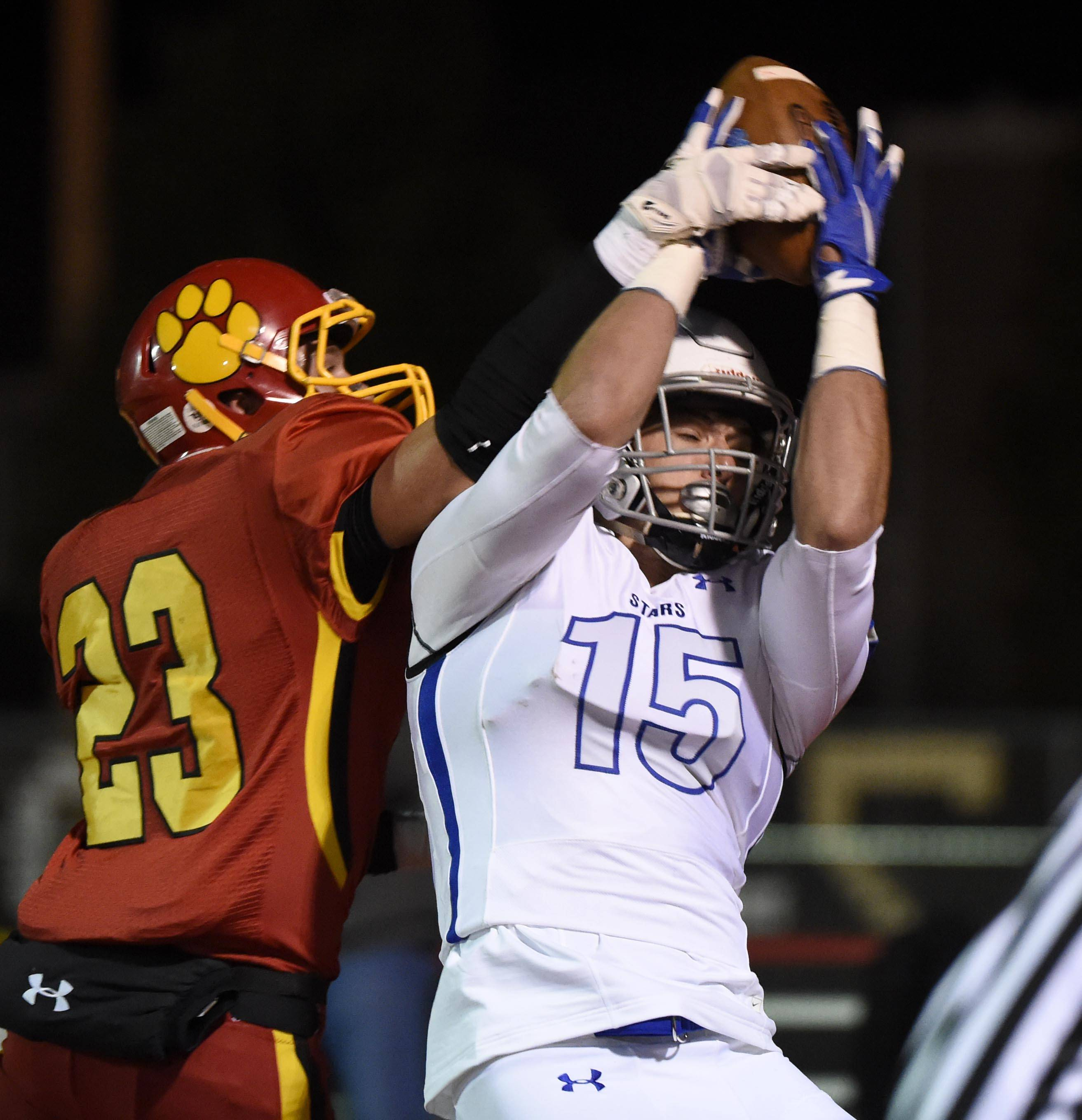 St. Charles North's Griffin Hammer catches a touchdown pass as Batavia's Thomas Stuttle defends Friday in Batavia.