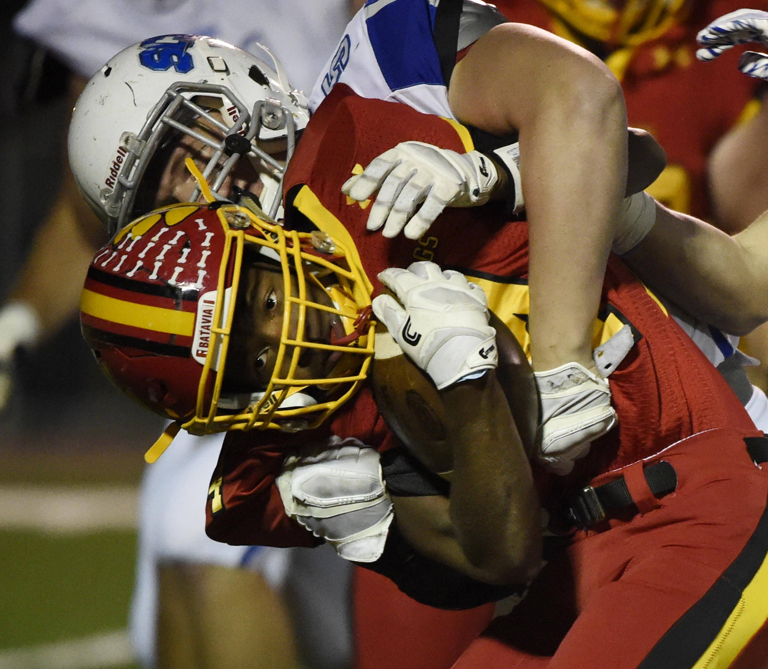 Batavia's Reggie Phillips gets wrapped up by St. Charles North's Jack Wolf Friday in Batavia.