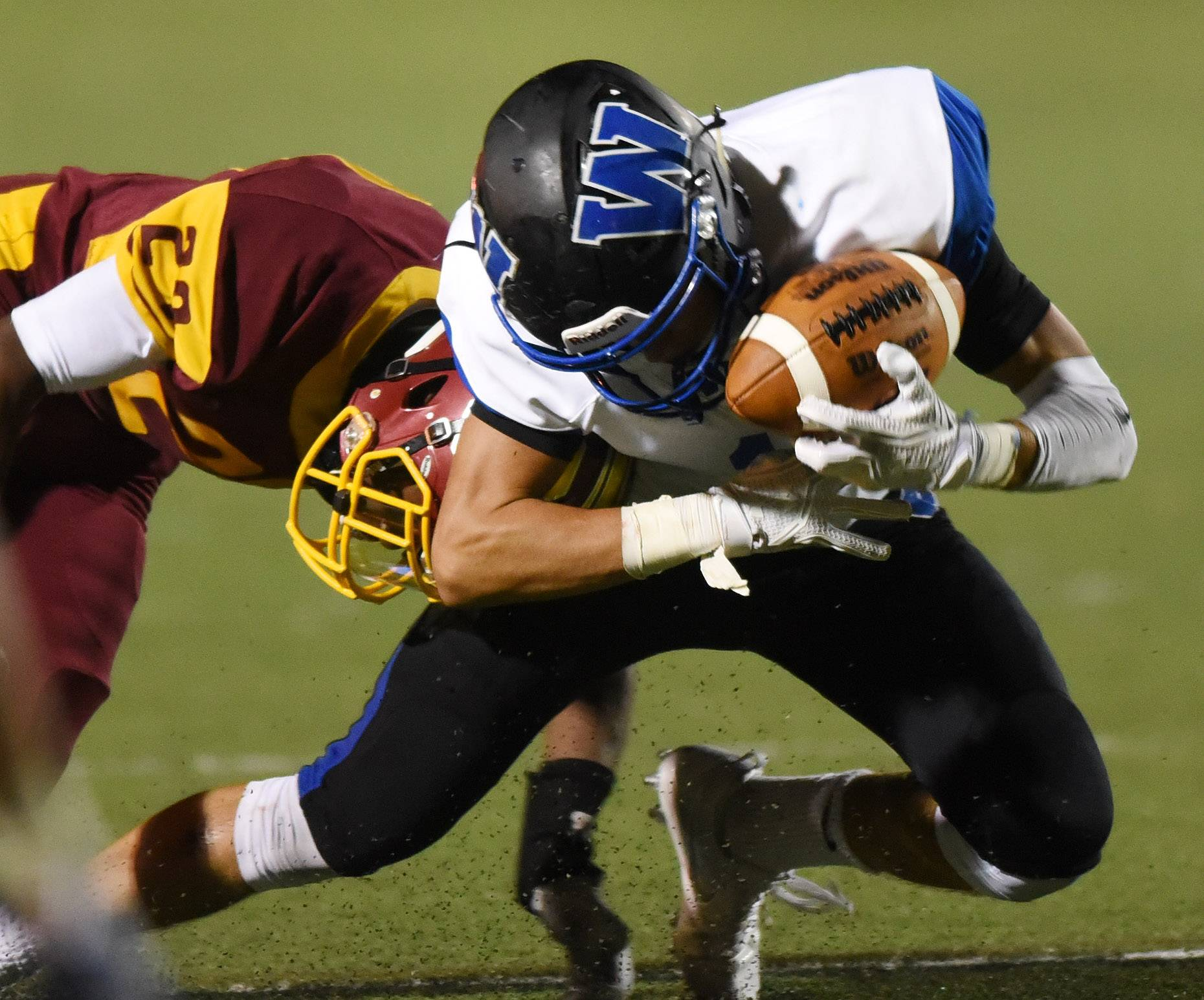 Wheeling's T.J. Best, here grabbing a pass in front of Schaumburg's Anthony Nix, made a big difference by excelling as a receiver this fall.