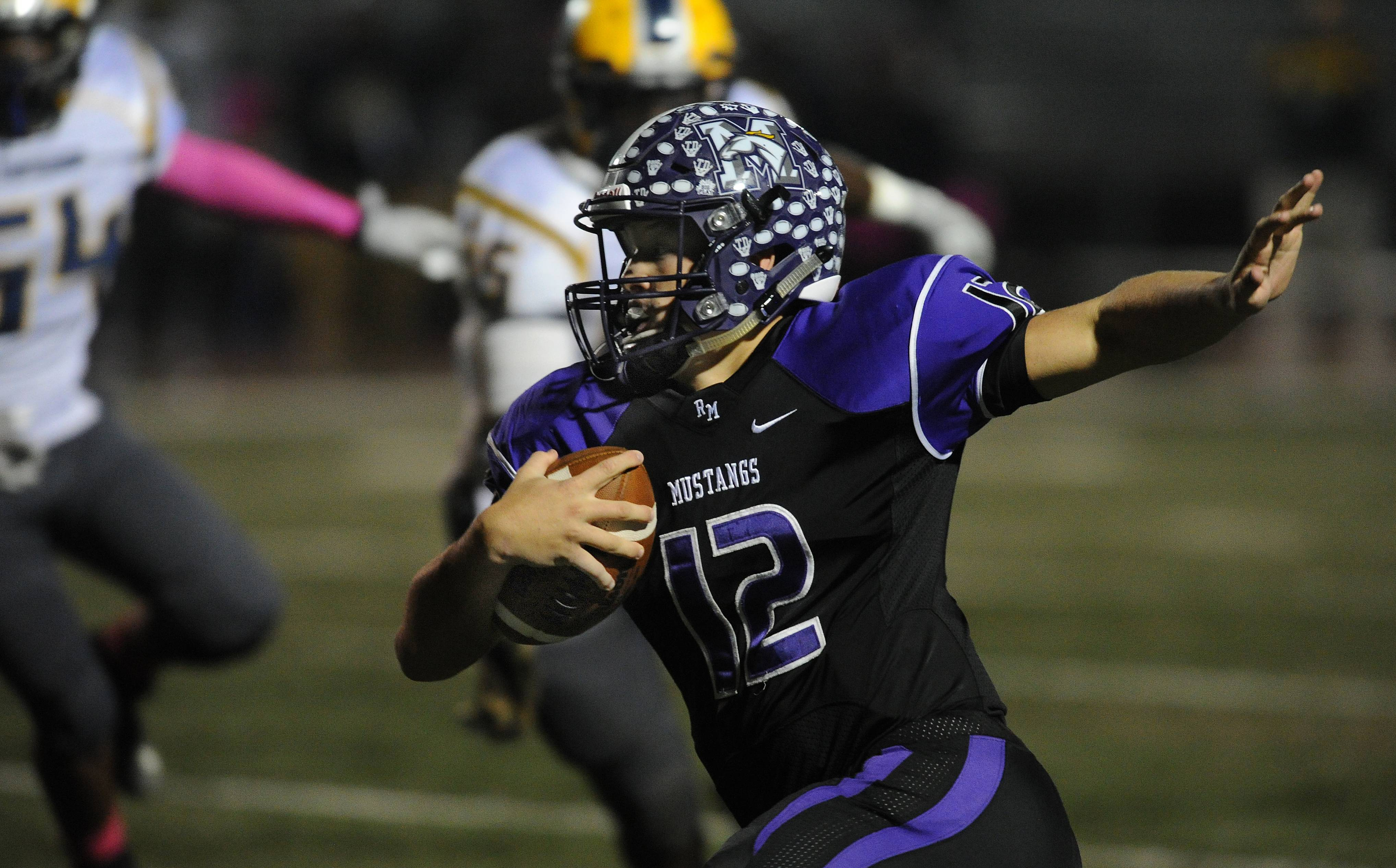 Rolling Meadows' Asher O'Hara keeps the ball for short yardage in the first quarter against Thornwood.