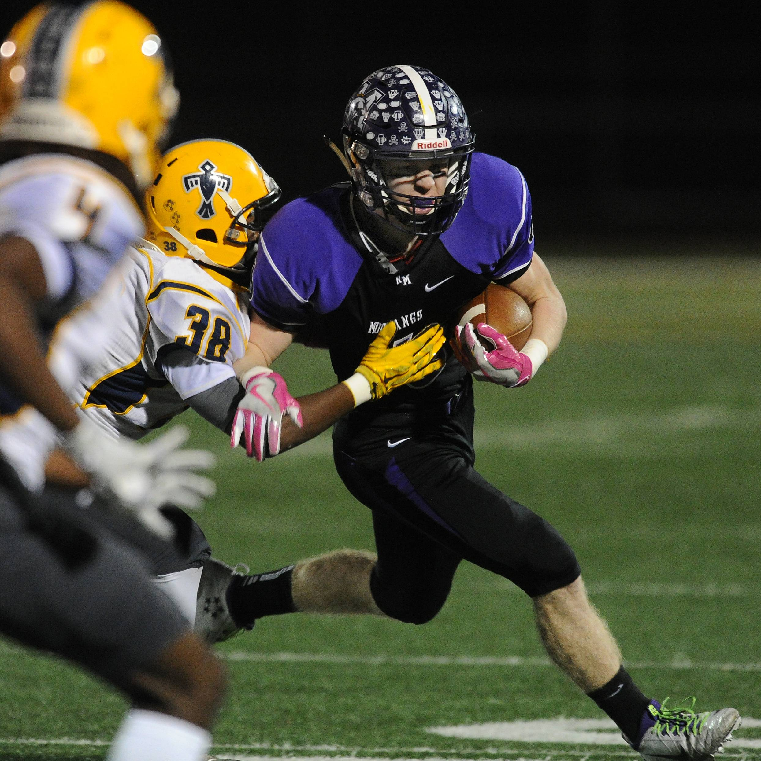 Rolling Meadows' Nick Delporte runs for yardage in the first quarter despite pressure from Thornwood's Bre Love in the first round of the Class 7A football playoffs at Meadows.