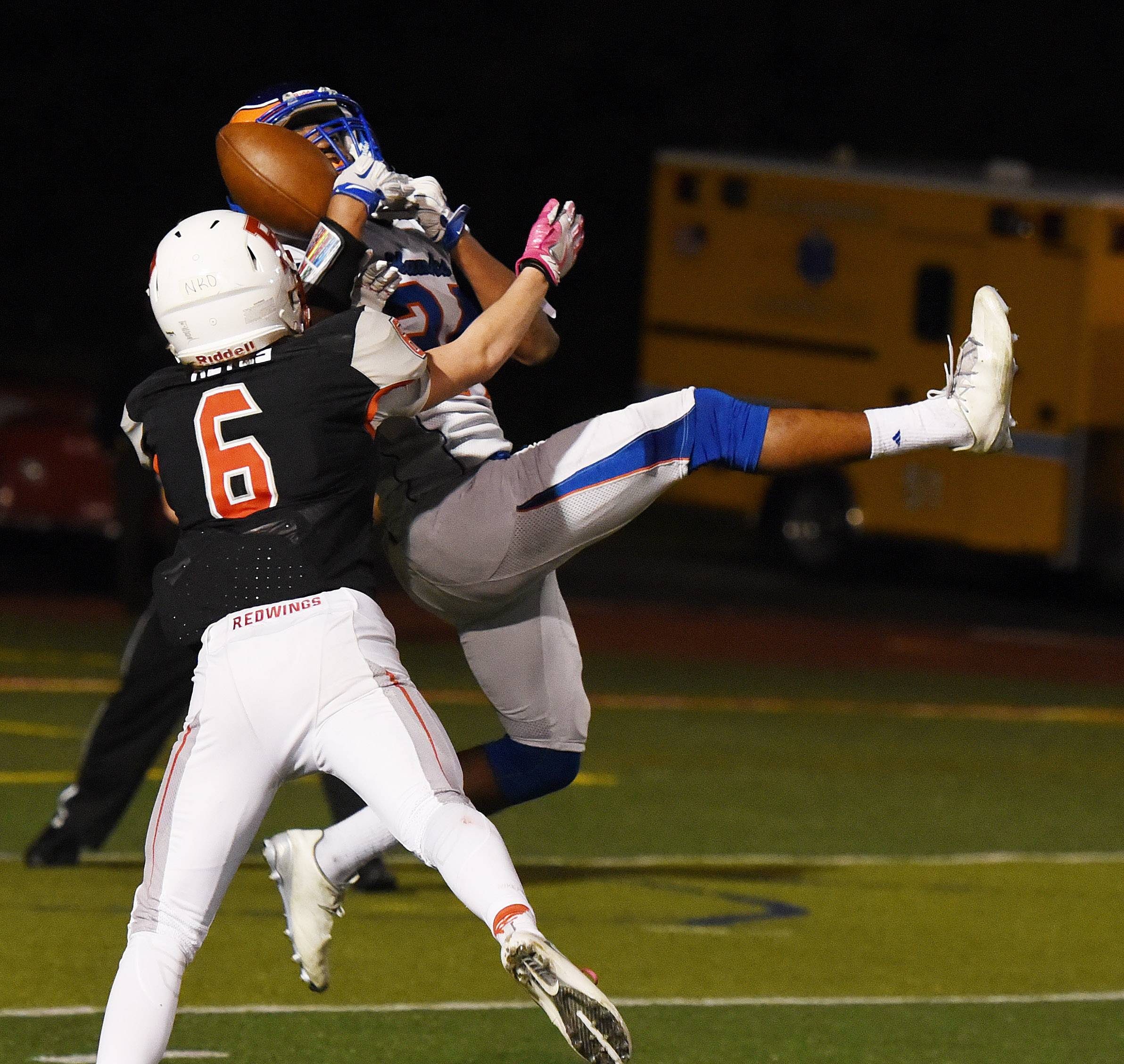 Benet's Nicholas Keyes (6) and Hoffman Estates' Trevon Hall (24) vie for a pass during the Hoffman Estates at Benet football game Friday.