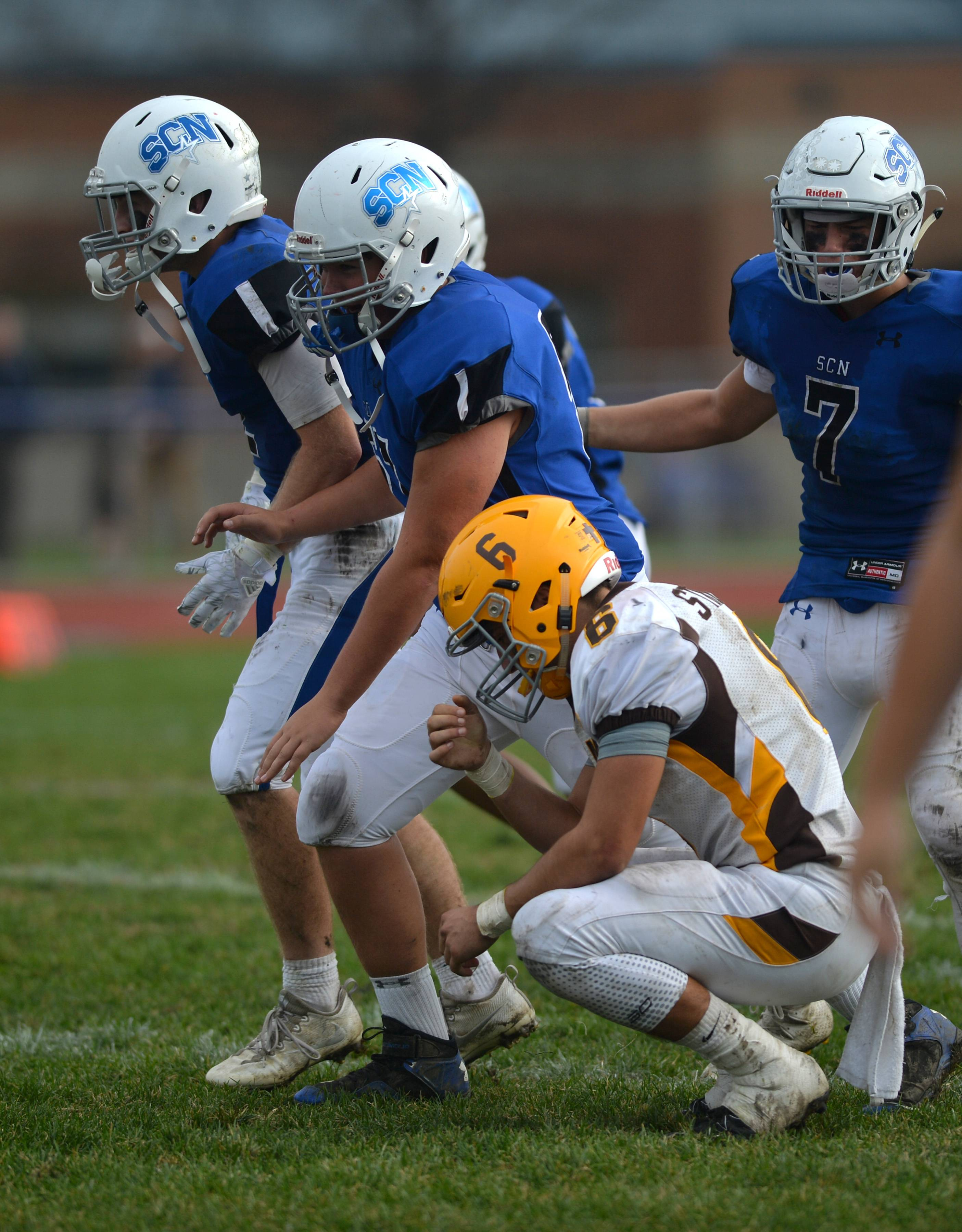 St. Charles North players celebrate as Carmel quarterback Jeremy Strutzel contemplates the North Stars' 31-24 double overtime win in a HSA Class 7A playoff game Saturday in St. Charles.
