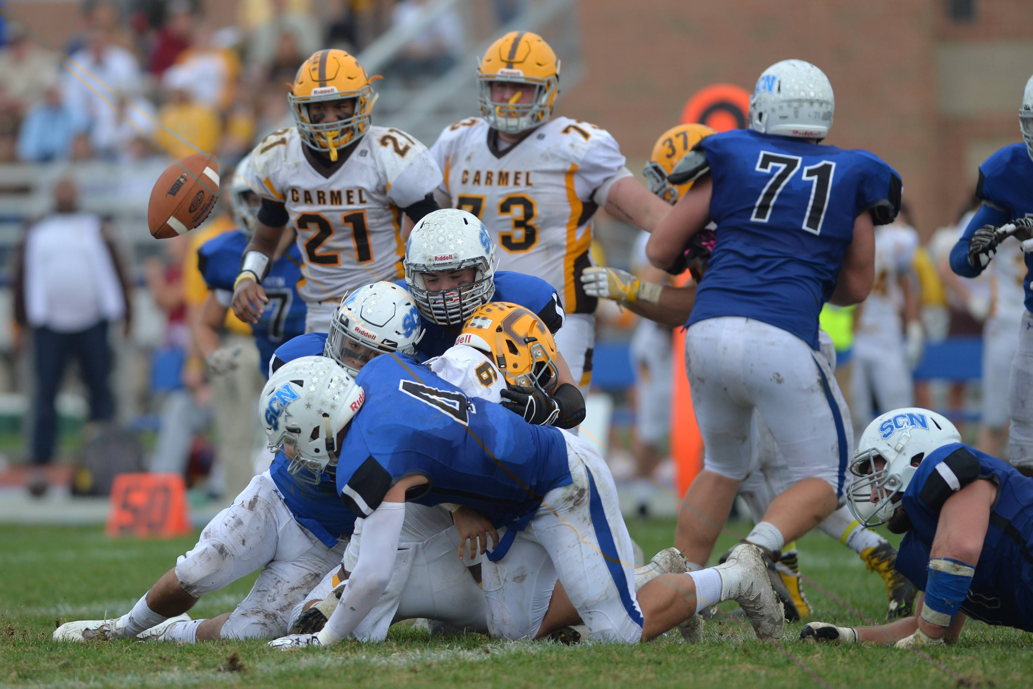 St. Charles North defenders force a Carmel fumble which was returned for a touchdown in the third quarter of the North Stars' 31-24 double overtime win over Carmel Saturday in St. Charles.