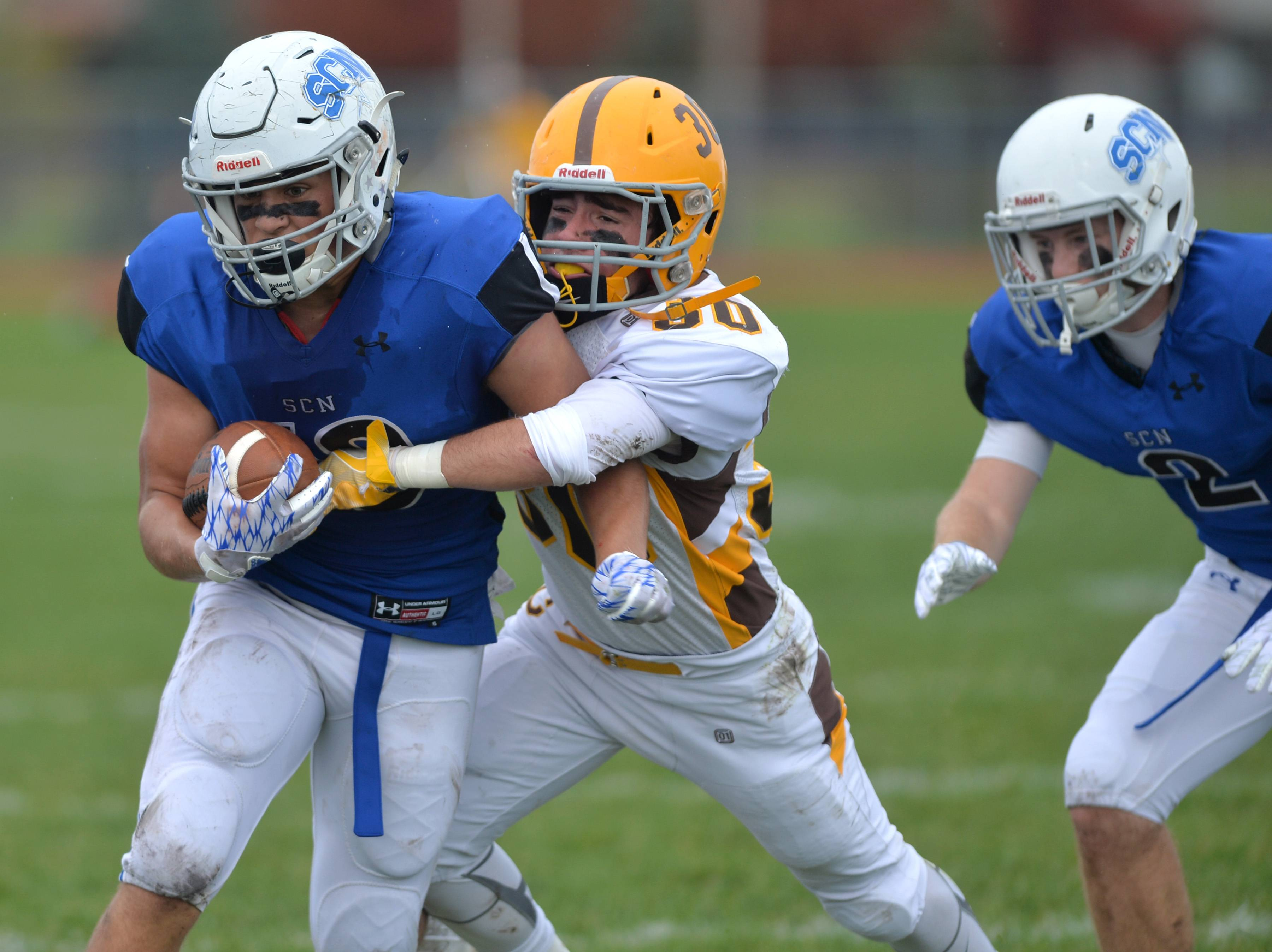 St. Charles Norths Antonio Trippiedi fights for yardage as Carmel defender John Misak makes the stop in the second quarter of their IHSA Class 7A playoff age Saturday in St. Charles. The North Stars advanced with a 31-24 double overtime win.