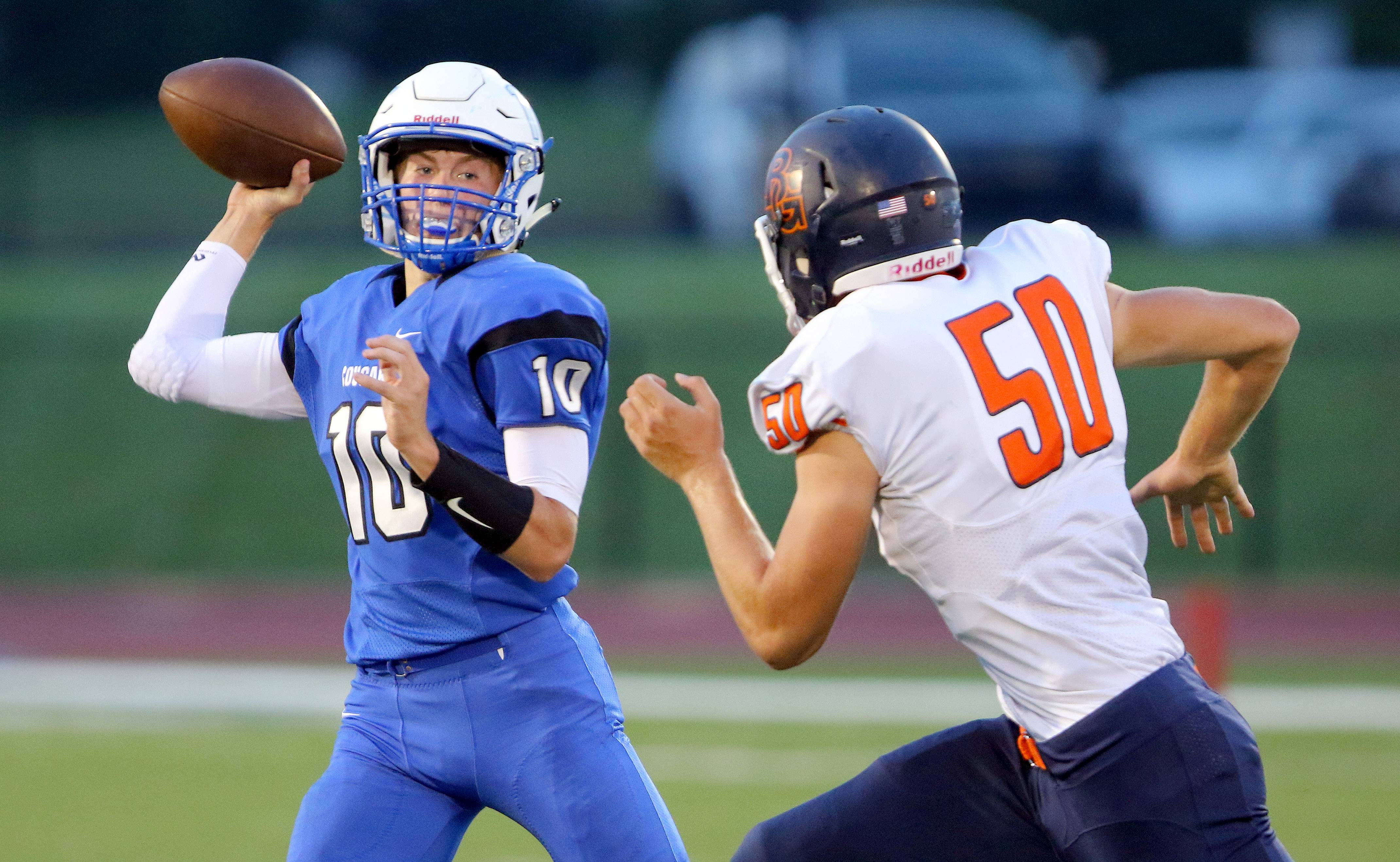 Vernon Hills' Kyle Hull looks to pass as Buffalo Grove's Justin Gold pursues during regular-season play at Vernon Hills. The Cougars travel to Nazareth Academy for a 1 p.m. Saturday second-round playoff matchup.