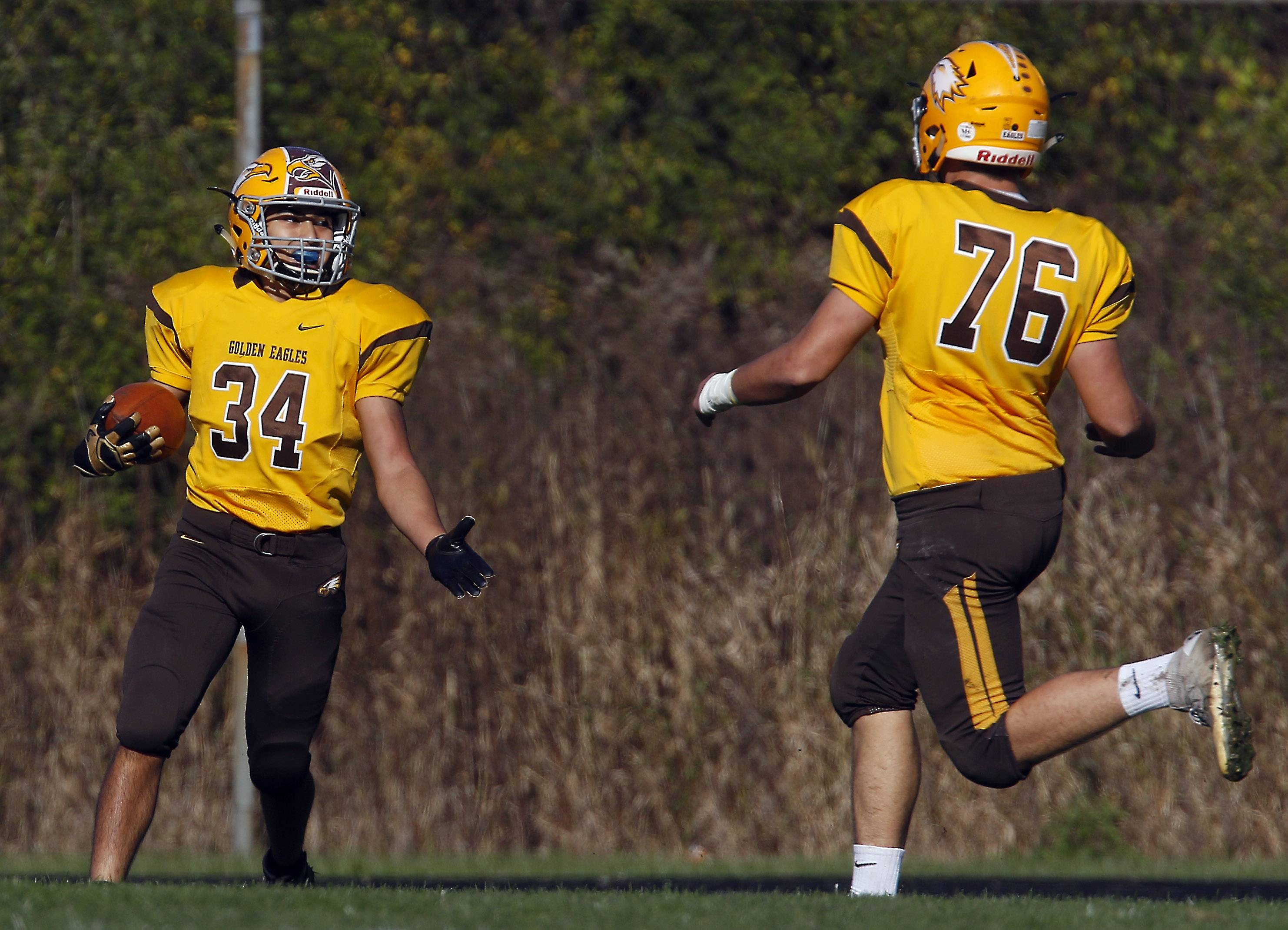 Jacobs' David Butros (34) celebrates a touchdown with teammate Cade Portell Saturday in Algonquin.