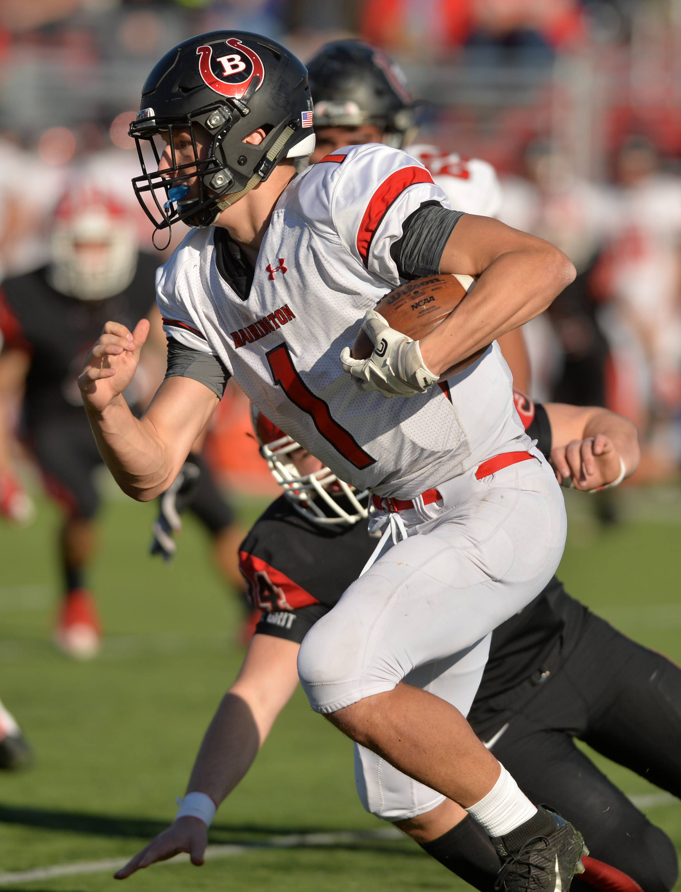 Barrington quarterback Josh Babicz breaks through the Maine South defense for a long run in Class 8A playoff action Saturday in Park Ridge. The Broncos fell to the Hawks 42-27.