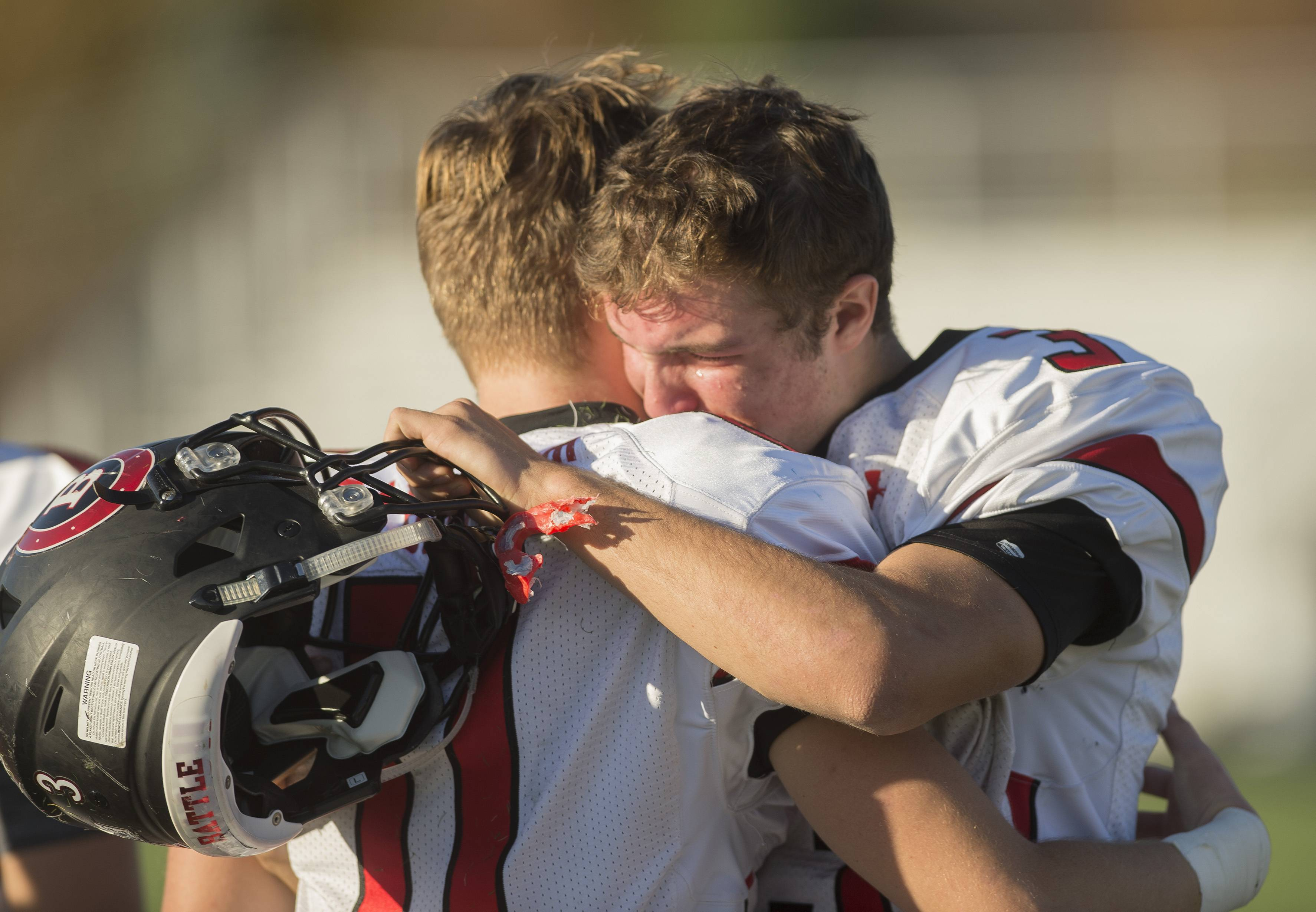 Barrington quarterback Ray Niro, right, hugs wide receiver Griffin Gabbert after the Broncos fell to Maine South 42-27 in a second-round playoff matchup in Class 8A.