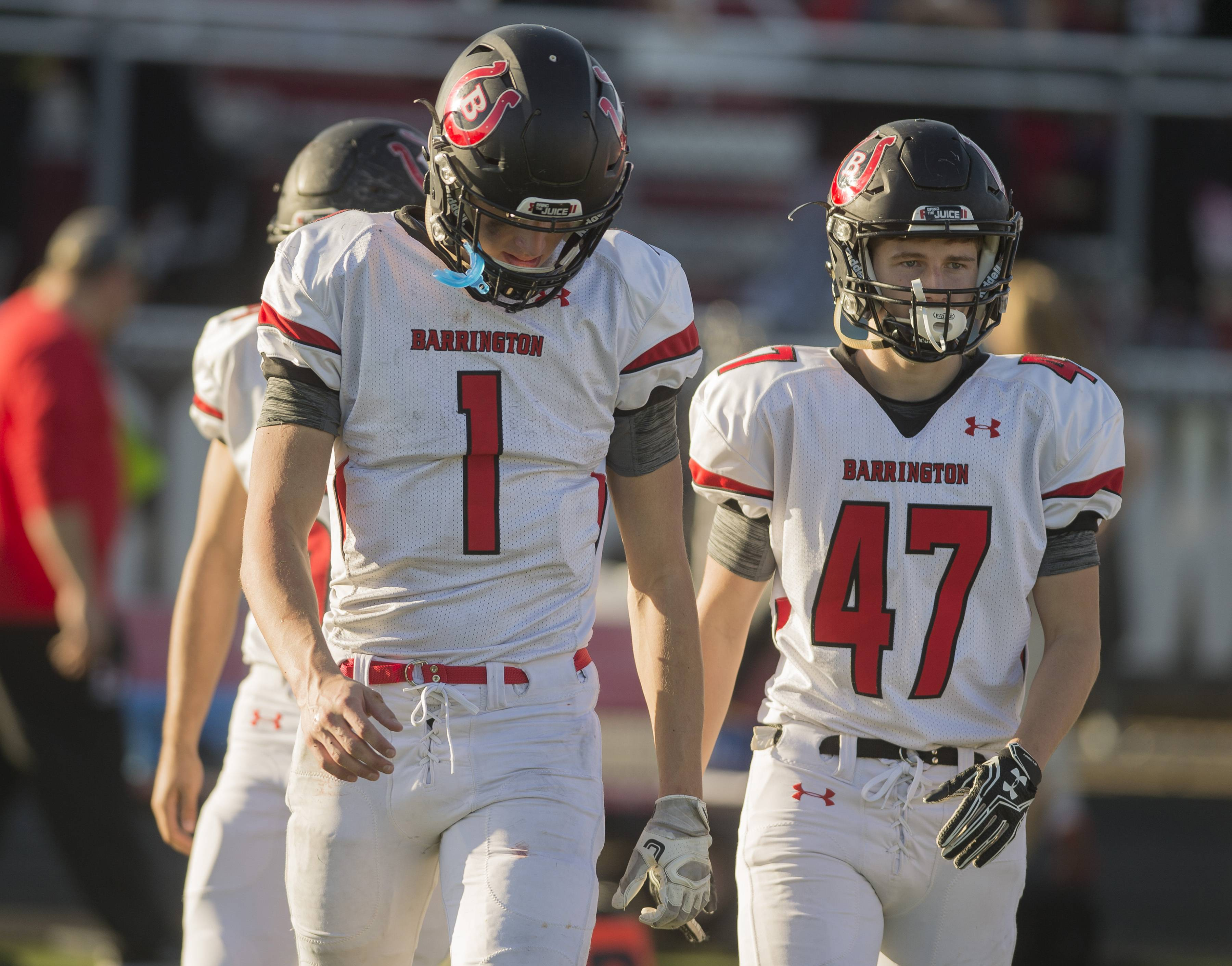 Barrington quarterback Josh Babicz and Jack Young leave the field after the Broncos came up short 42-27 on Saturday at Maine South.