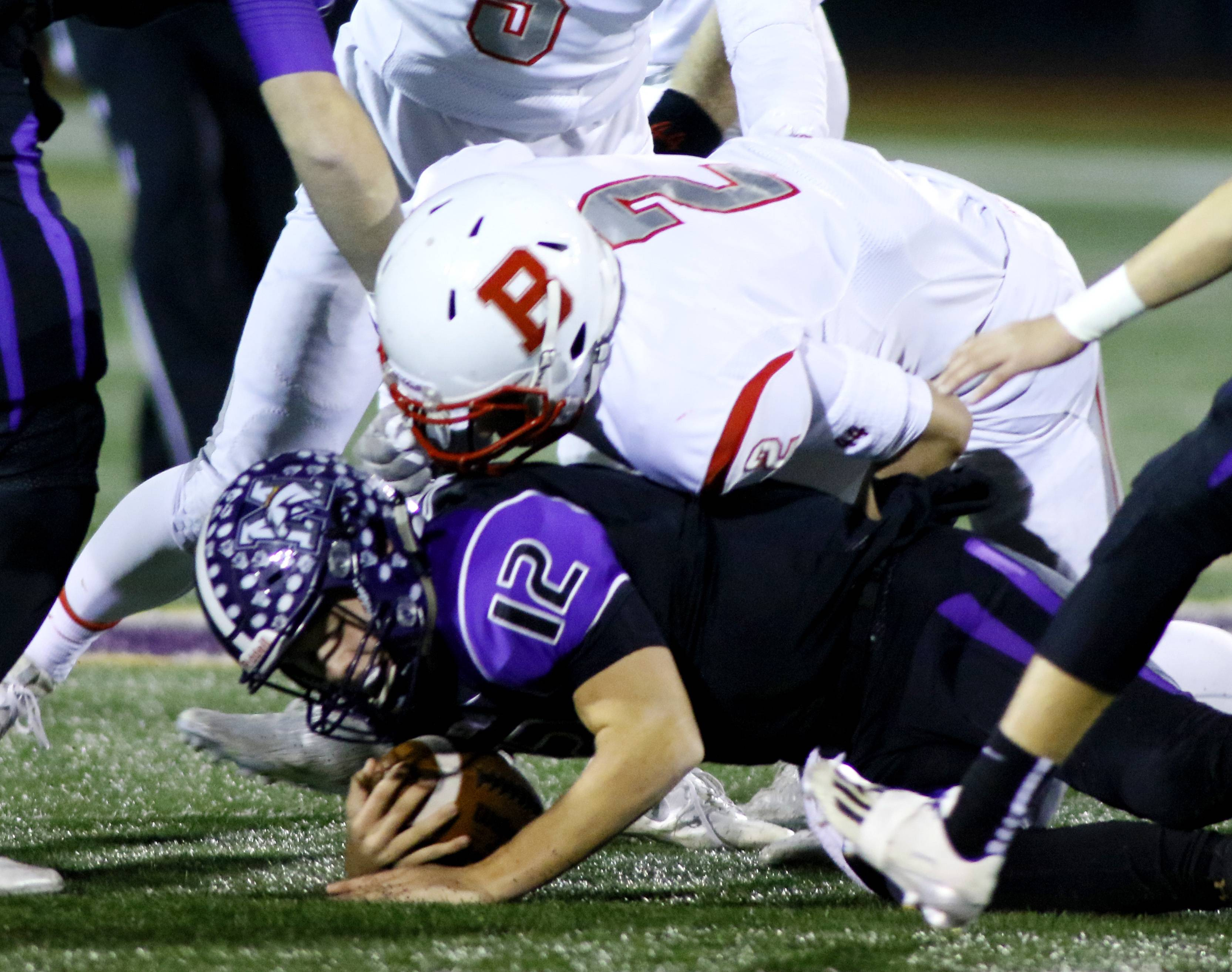 Rolling Meadows quarterback Asher O'Hara (12) is brought down by Benet Academy's Danny O'Malley (2) during first half action against Rolling Meadows during Class 7A football action in Rolling Meadows.