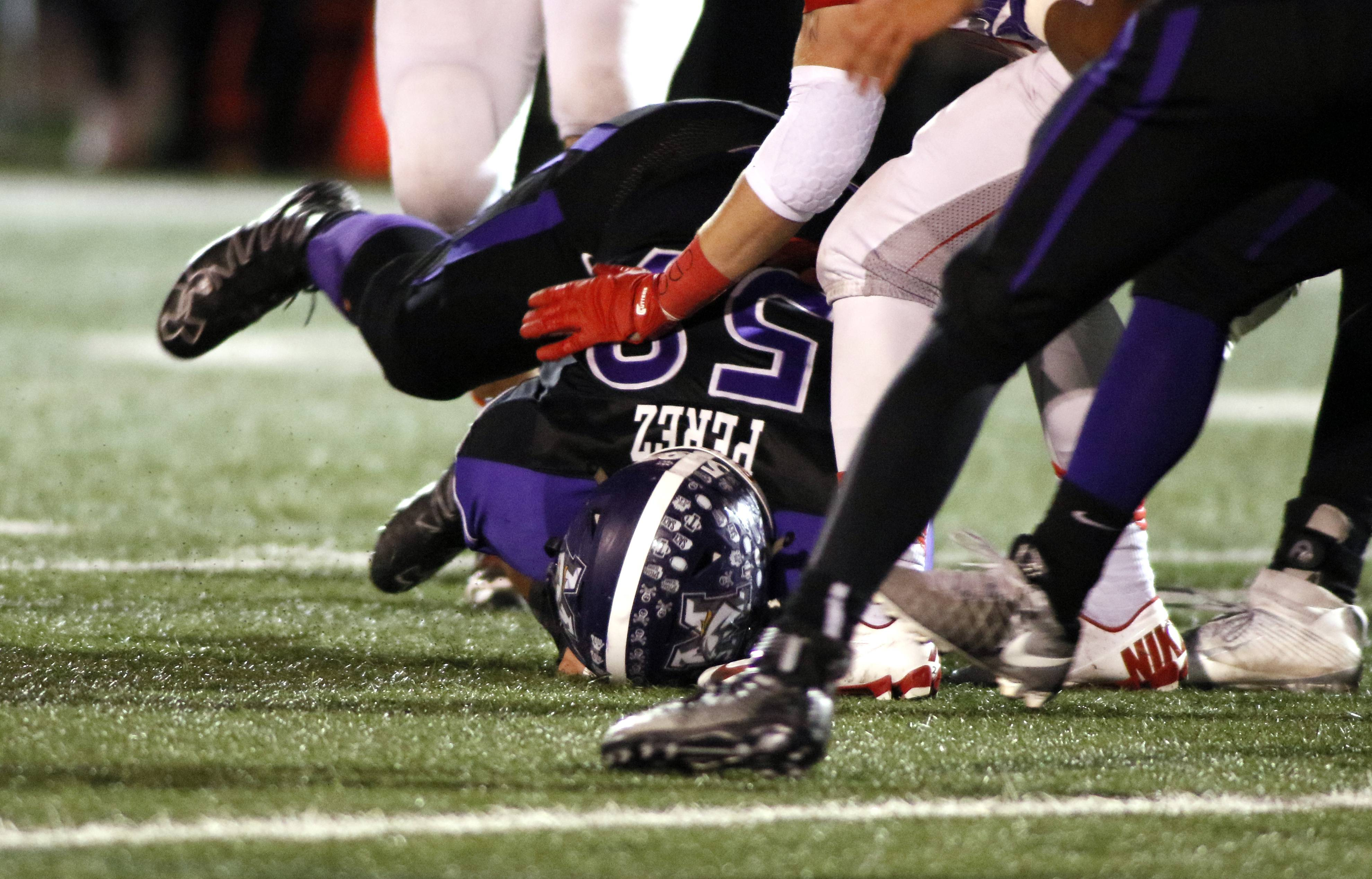 Rolling Meadows' Marco Perez recovers a first half fumble against Benet Academy during Class 7A football action in Rolling Meadows.
