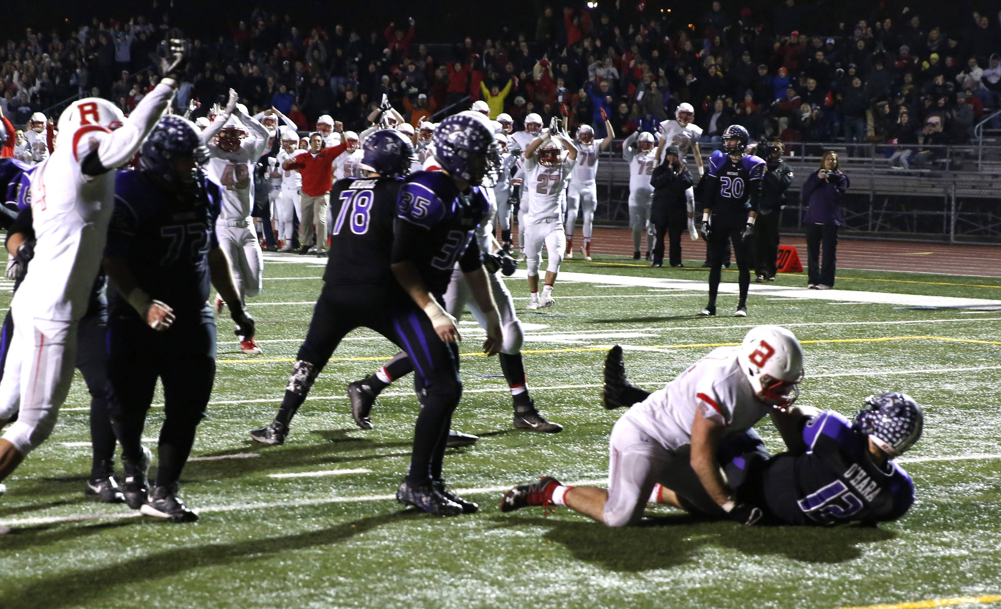 Rolling Meadows quarterback Asher O'Hara (12) is brought down for a safety in the second half against Benet Academy during Class 7A football action in Rolling Meadows.