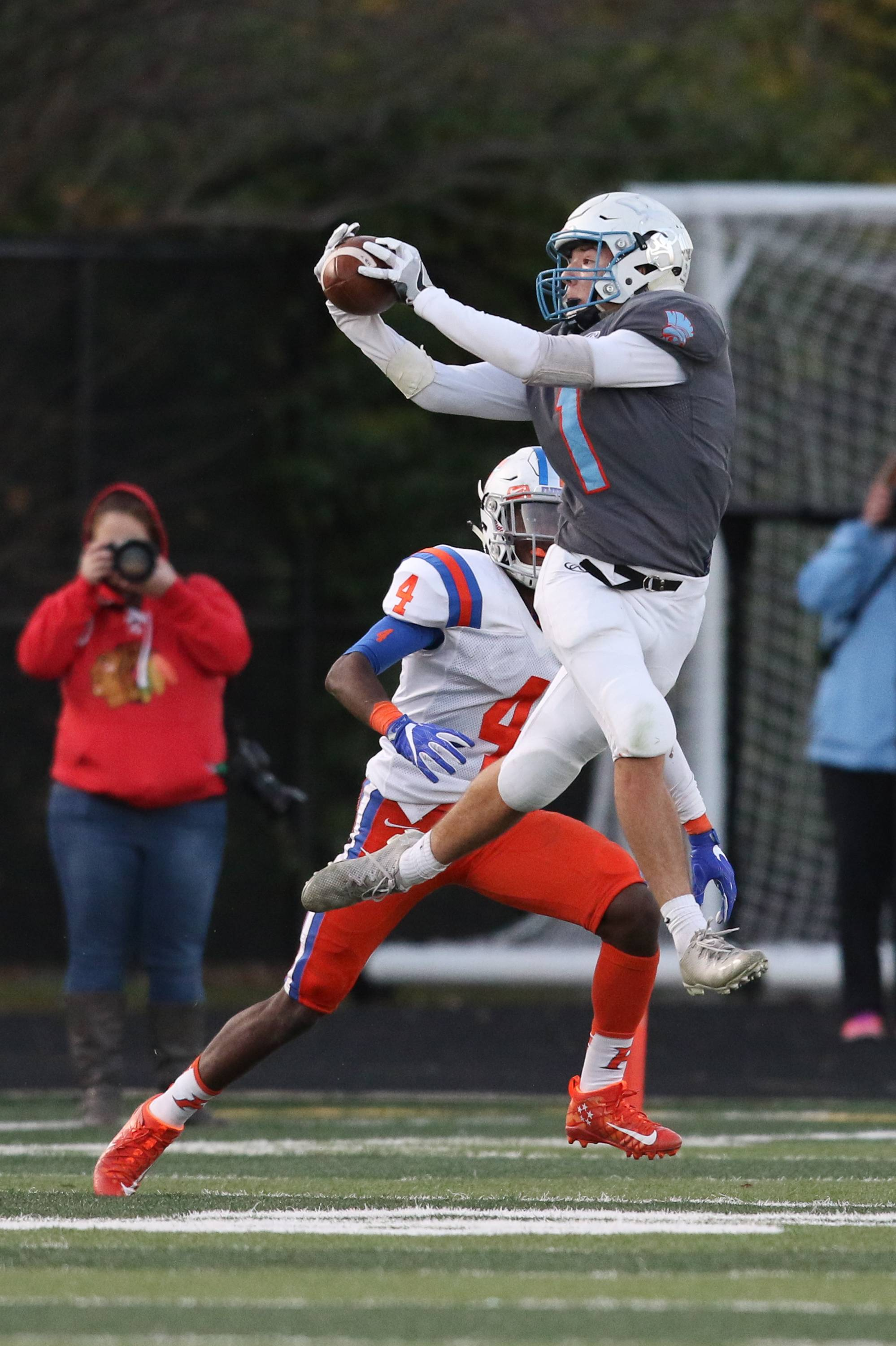 Willowbrook wide receiver Jonathan Kelso (1) makes a leaping reception against East St. Louis defensive back Jeff Thomas (4) during a 7A quarterfinal state playoff game at Willowbrook High School in Villa Park, IL on Saturday, November 12, 2016
