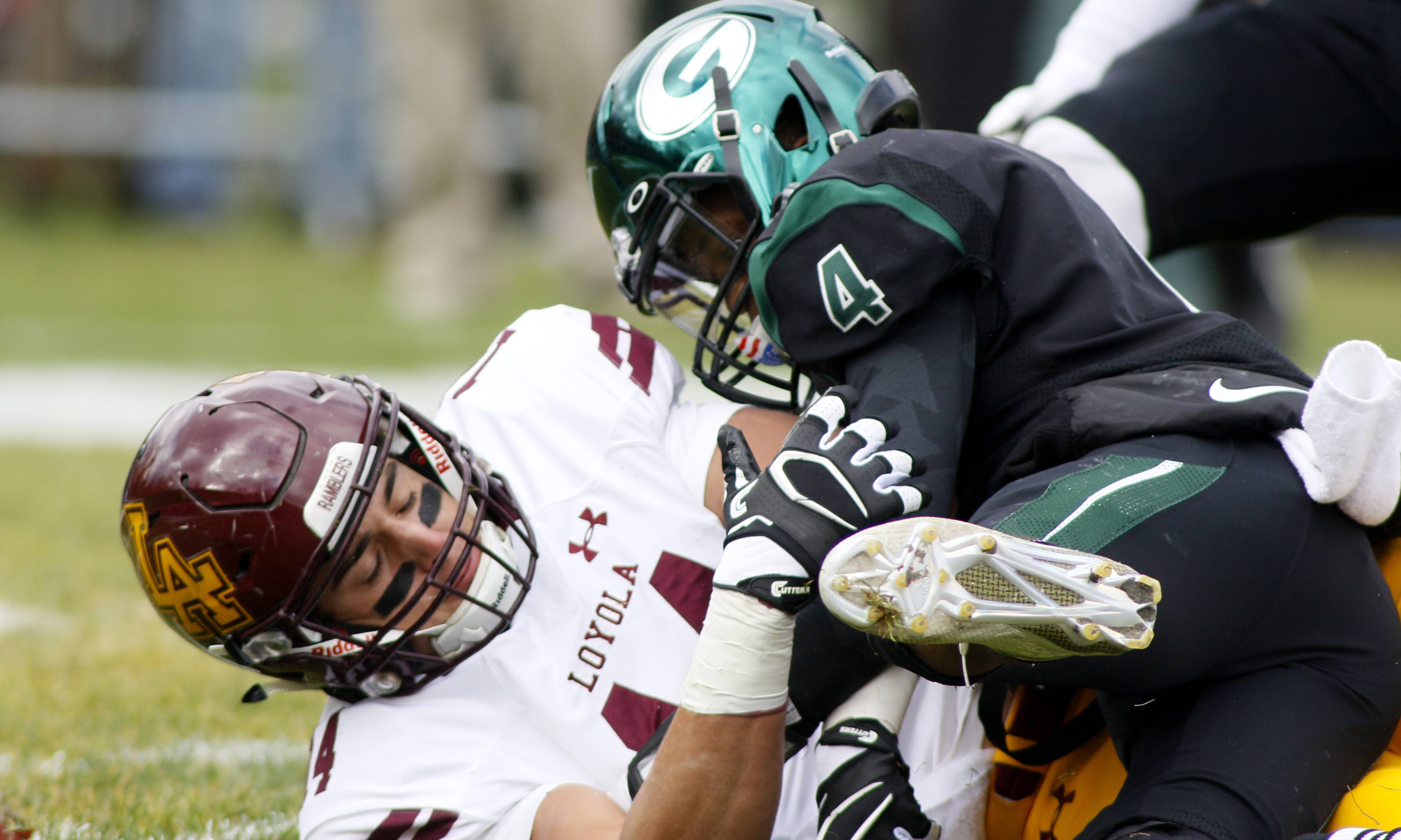 Loyola Academy's Jake Marwede, left, is brought down by Glenbard West's Justice Bradley (4) during Class 8A semifinal playoff football action in Glen Ellyn.