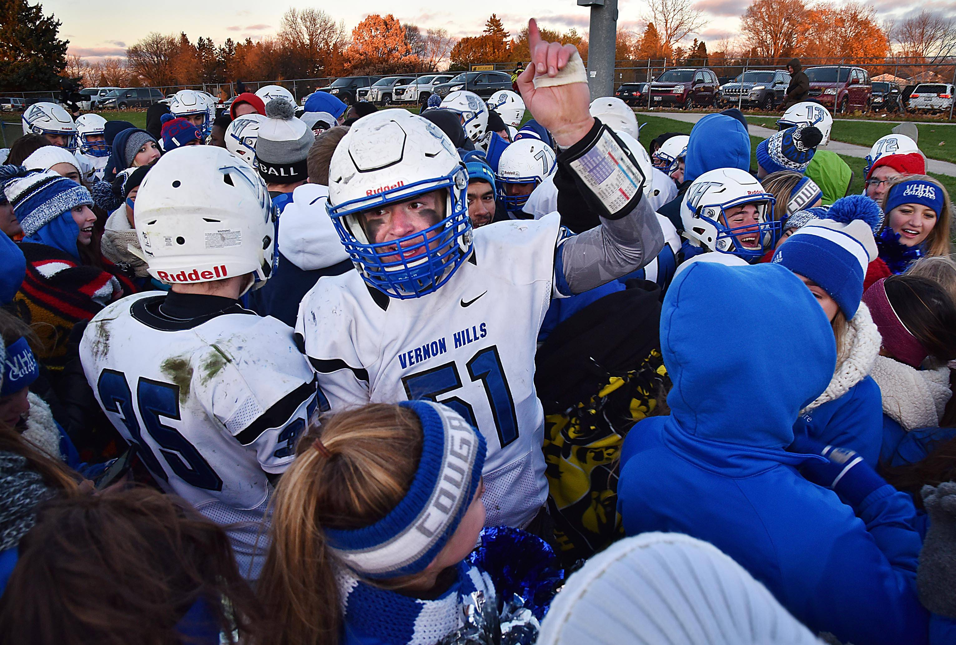 Vernon Hills' Andrew Smith and his teammates and classmates celebrate the Cougars' win against Sycamore on Saturday in the Class 5A football state semifinal game in Sycamore.