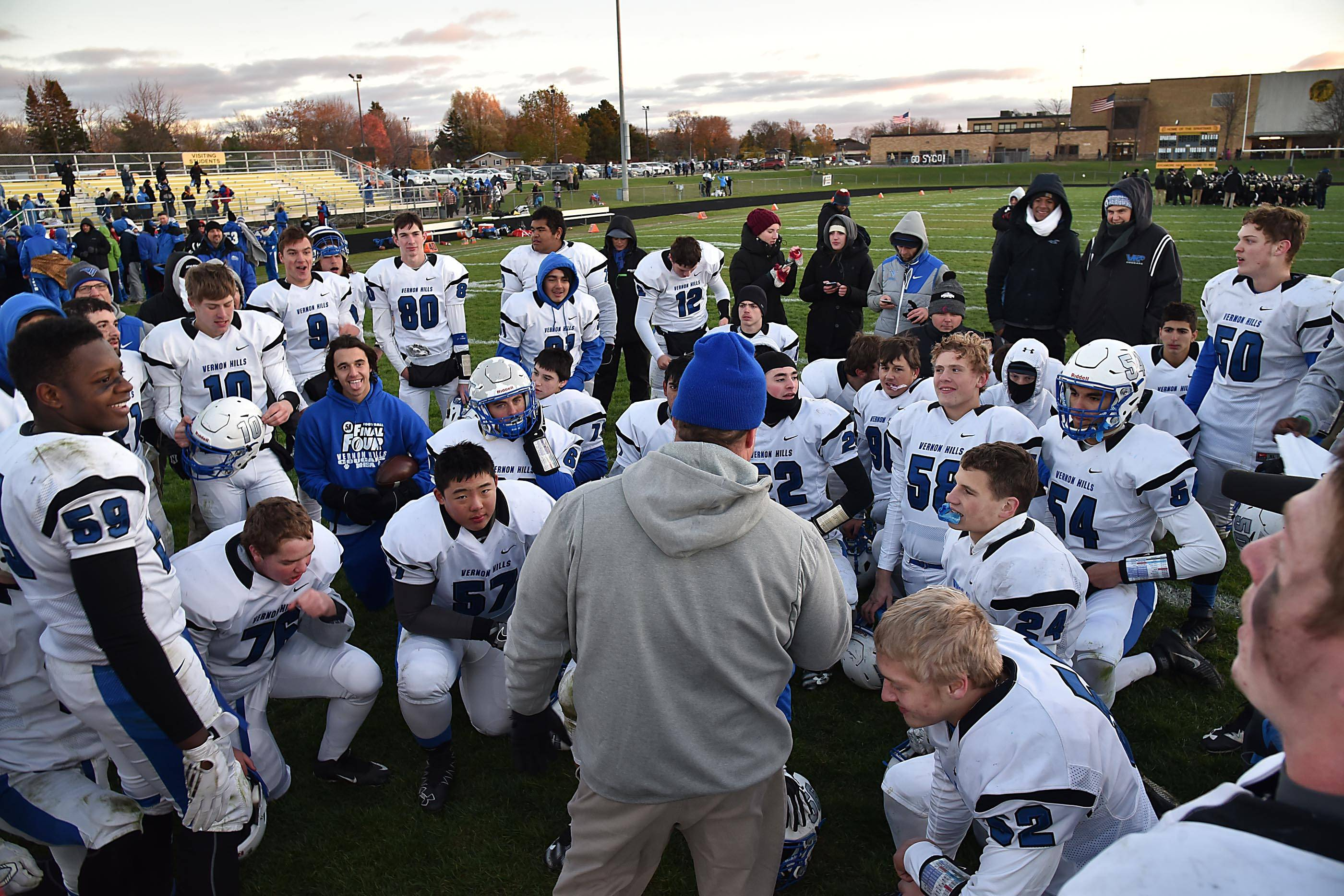 Vernon Hills players gather around their coach after beating Sycamore on Saturday in the Class 5A football state semifinal game in Sycamore.