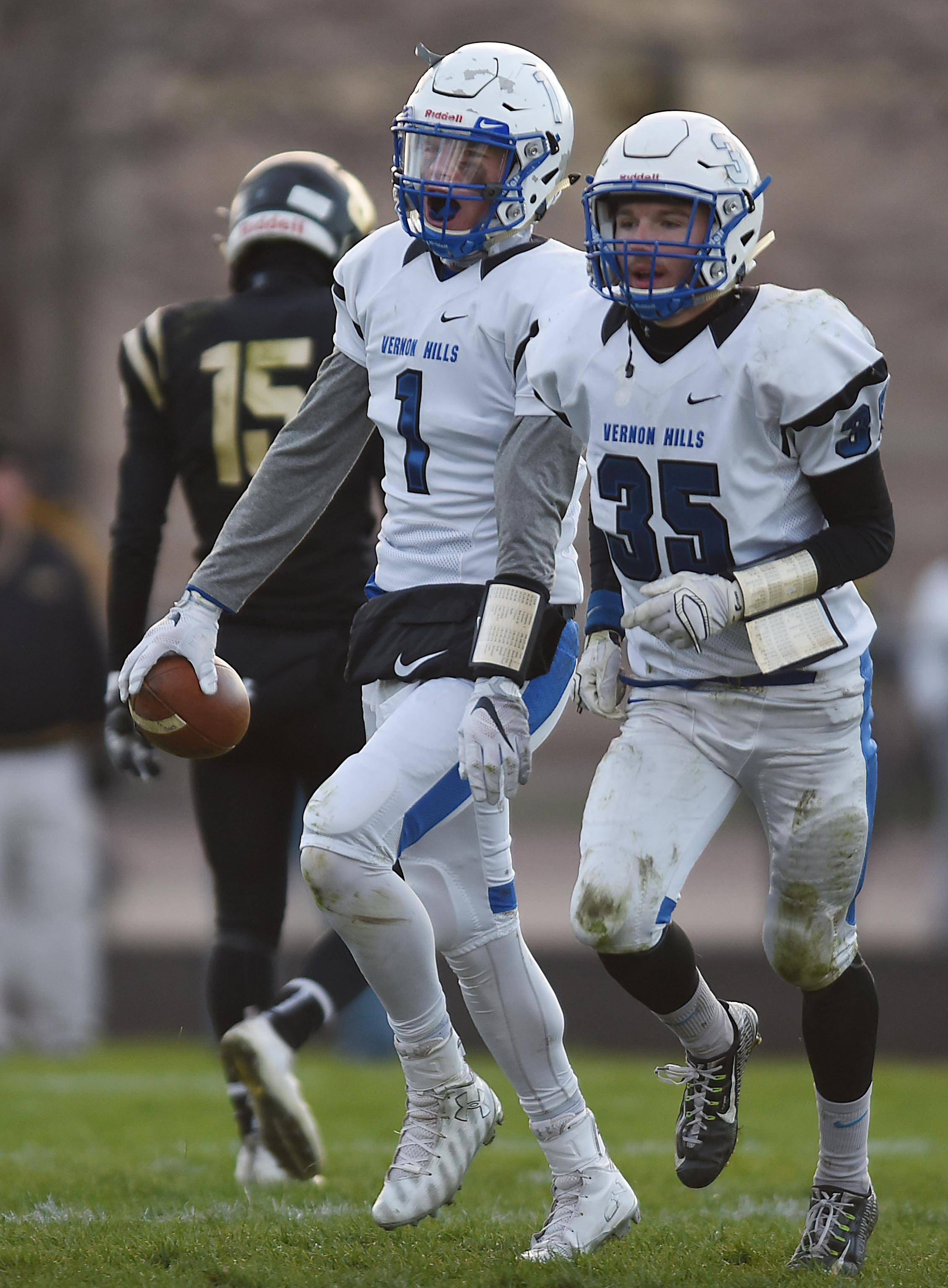 Vernon Hills' Chris Mariella laughs and yells after intercepting a Sycamore pass with just over four minutes left Saturday in the Class 5A football state semifinals in Sycamore. With him is teammate Trey Hommer.